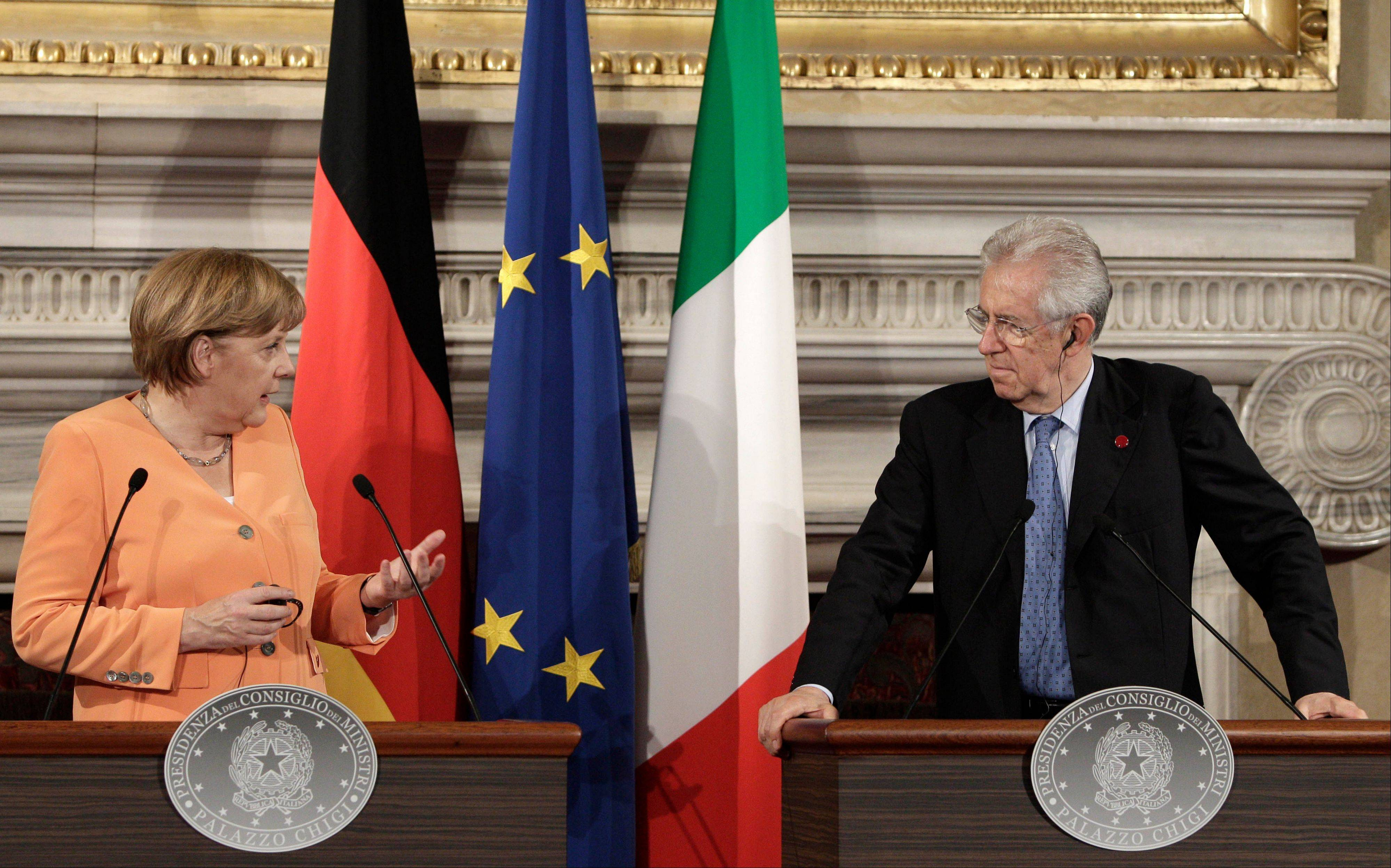 German Chancellor Angela Merkel, left, and Italian Premier Mario Monti speak at a press conference during a bilateral meeting at Villa Madama in Rome, Wednesday.