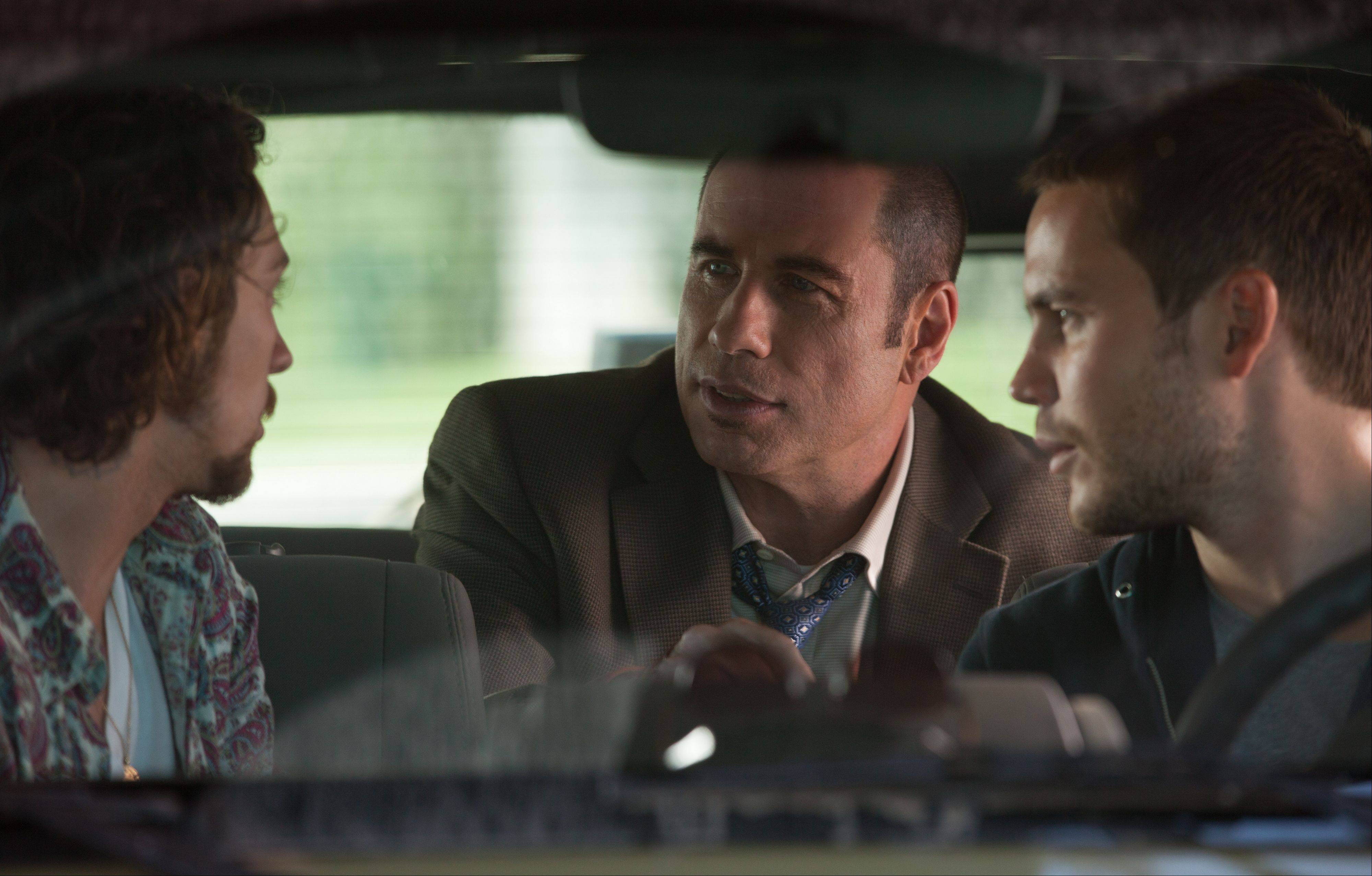 "Ben (Aaron Johnson), left, and Chon (Taylor Kitsch), right, chat with a corrupt federal officer (John Travolta) in a rare quiet moment from Oliver Stone's thriller ""Savages."""