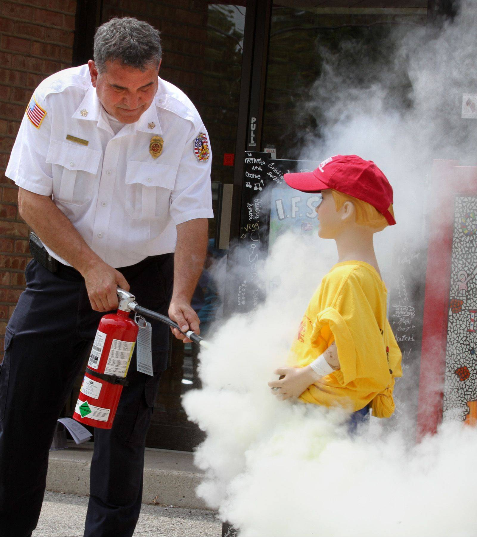 Hillside Fire Chief Michael Kuryla extinguishes a child-sized mannequin that was set ablaze Tuesday by a sparkler at a fireworks safety event sponsored by the Illinois Fire Safety Alliance to highlight the dangers of fireworks.