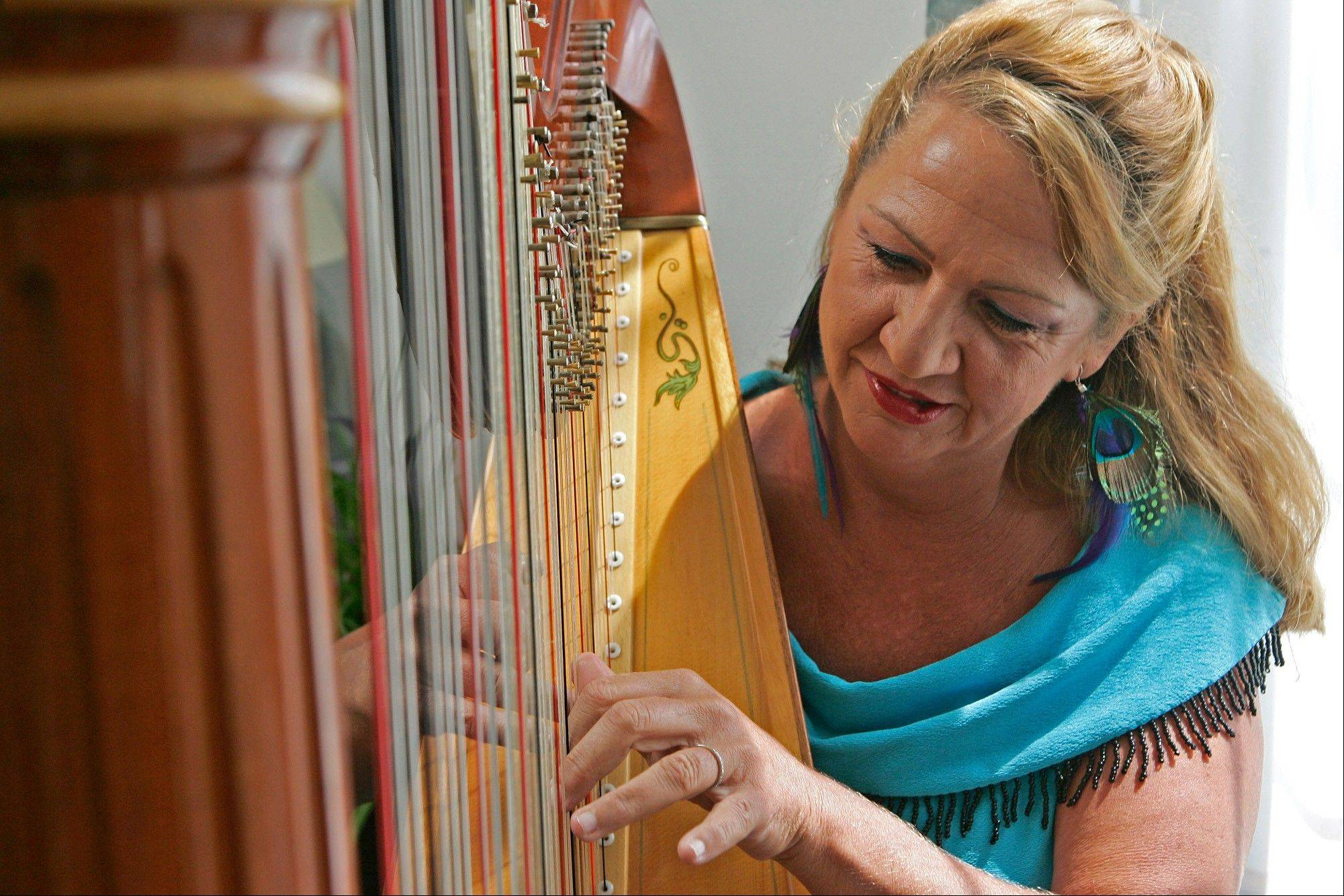 Harpist Nanette Felix plays one of her many harps at her home in Machesney Park.