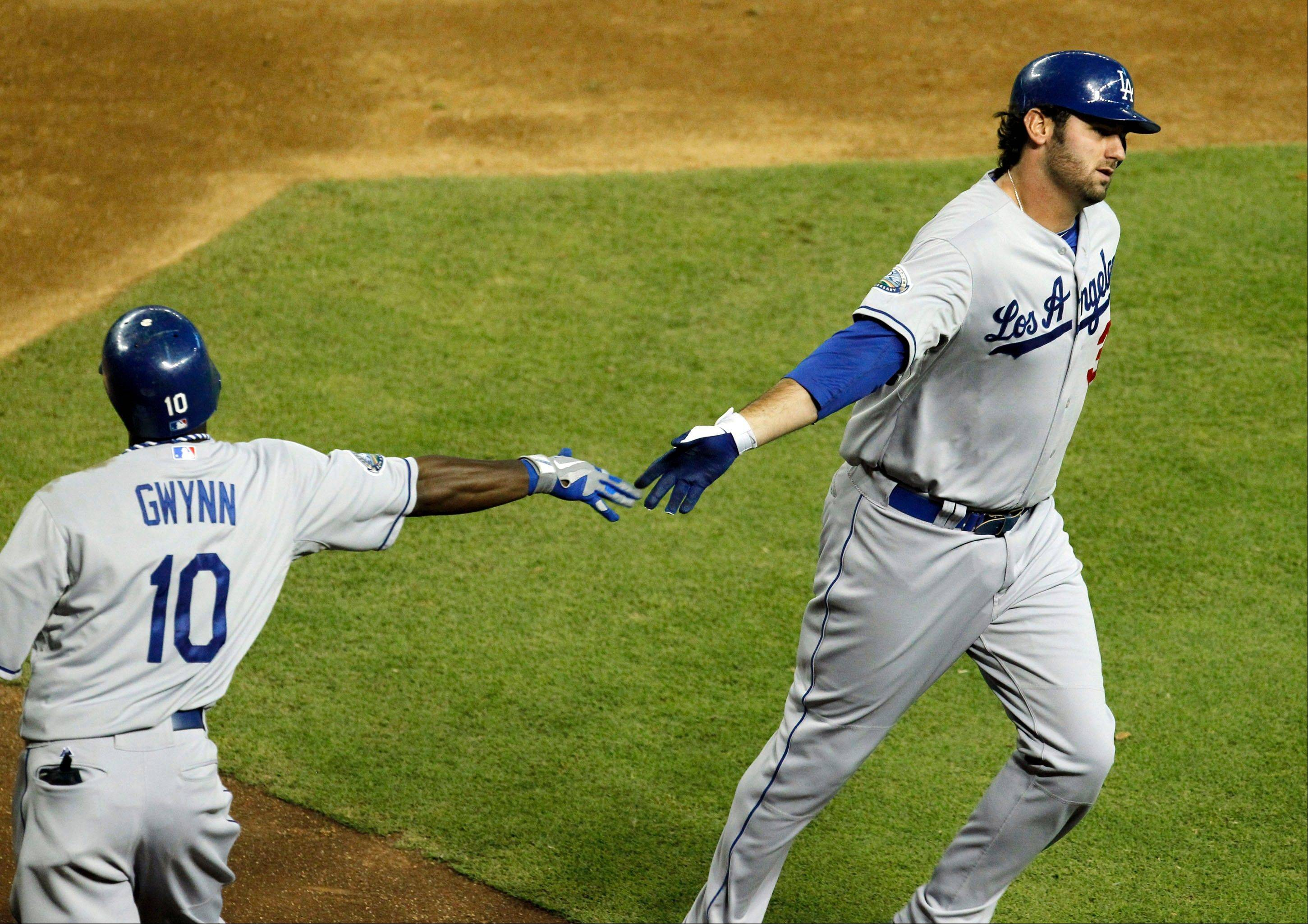 The Dodgers' Scott Van Slyke gets a hand slap from teammate Tony Gwynn Jr. for hitting a home run against the Arizona Diamondbacks in the fourth inning Thursday in Phoenix.