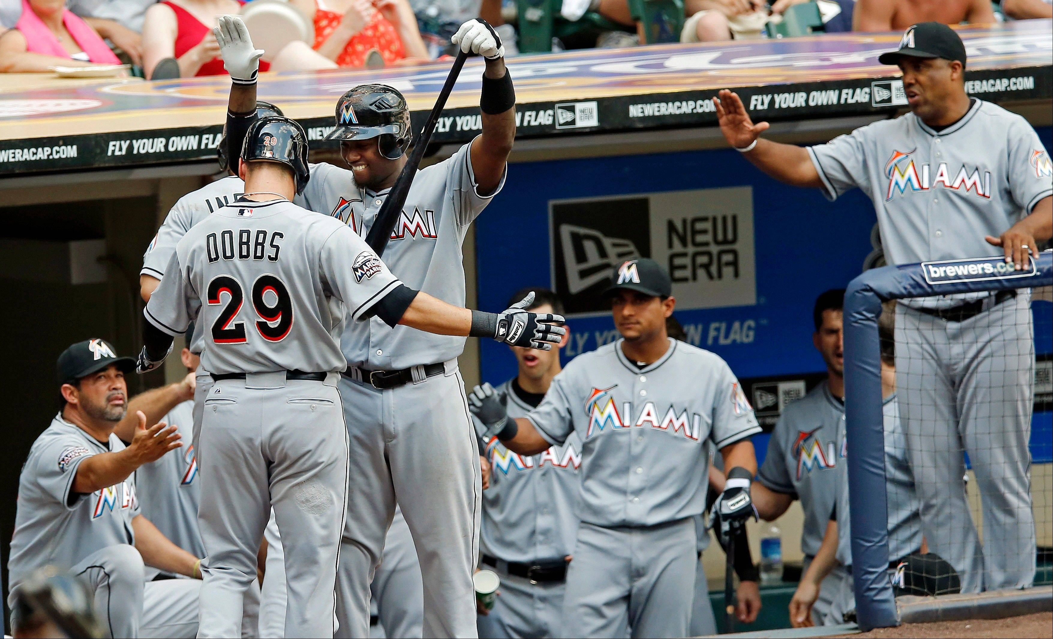 The Miami Marlins' Greg Dobbs is greeted by teammates at the dugout Thursday after hitting a two-run home run off Milwaukee Brewers pitcher Jose Veras during the ninth inning in Milwaukee. The Marlins won 4-0.