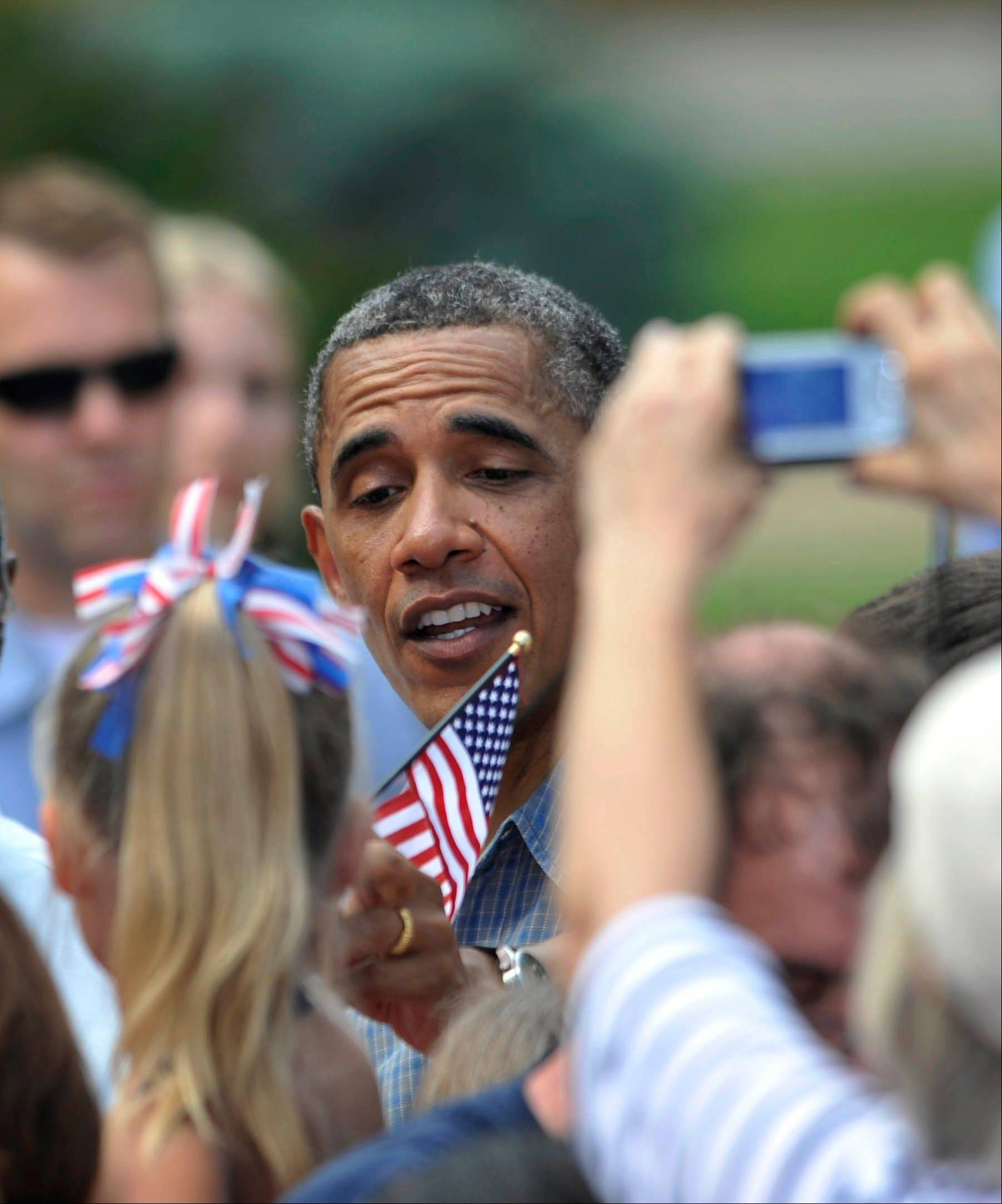 President Barack Obama takes a flag from Katelyn Maloy, 5, of Port Clinton, Ohio, after his speech at Washington Park in Sandusky, Ohio, Thursday. Obama is on a two-day bus trip through Ohio and Pennsylvania.