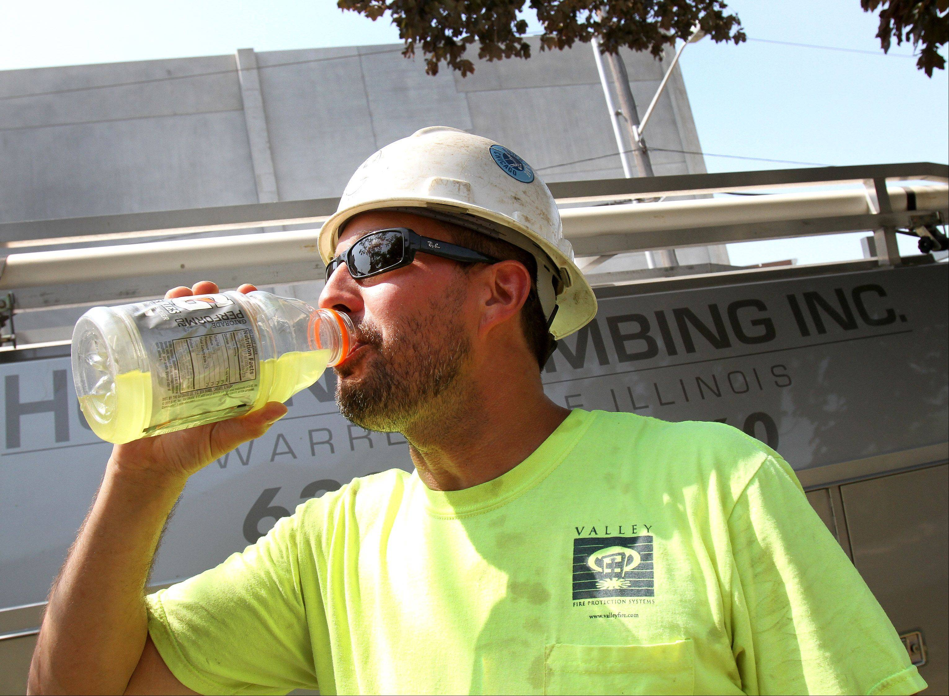 "Chuck Arwood of Hogan Plumbing takes a drink during a break Thursday at a Naperville construction site. ""We try to start early and get done early,"" he said of working on very hot days."