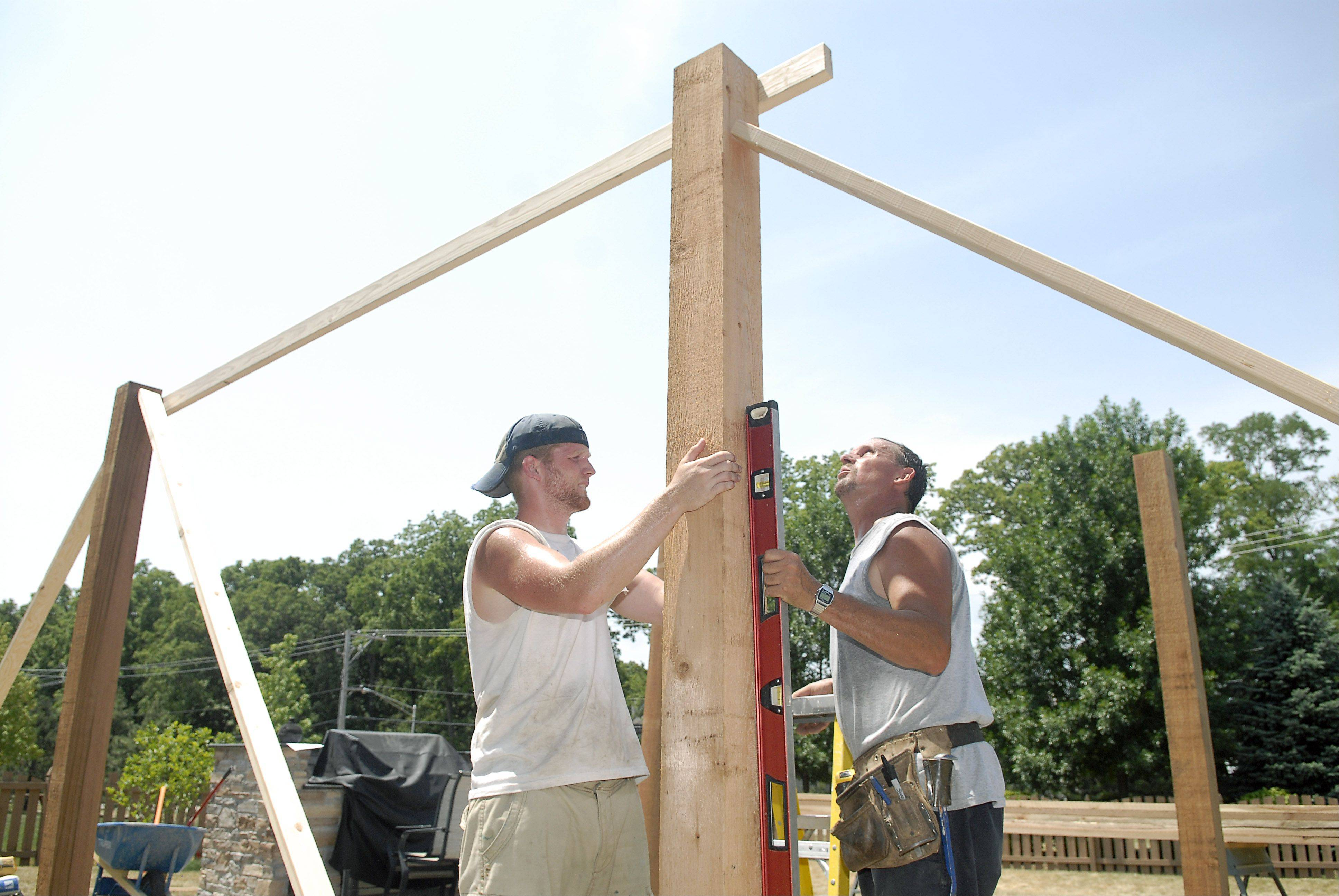 "Joe Weston, owner of JW Construction out of Lake Geneva, WI, and employee Max Hanna work on installing a pergola in the back yard of a Carpentersville home on Thursday, July 5. Weston likes to start early in order end early on hot days like this. He finds the extreme heat easier to deal with than extreme cold. ""The heat's easier to deal with. You can take a lot of breaks."" They manage the heat and are able to continue working in it by taking several water breaks in the shade."