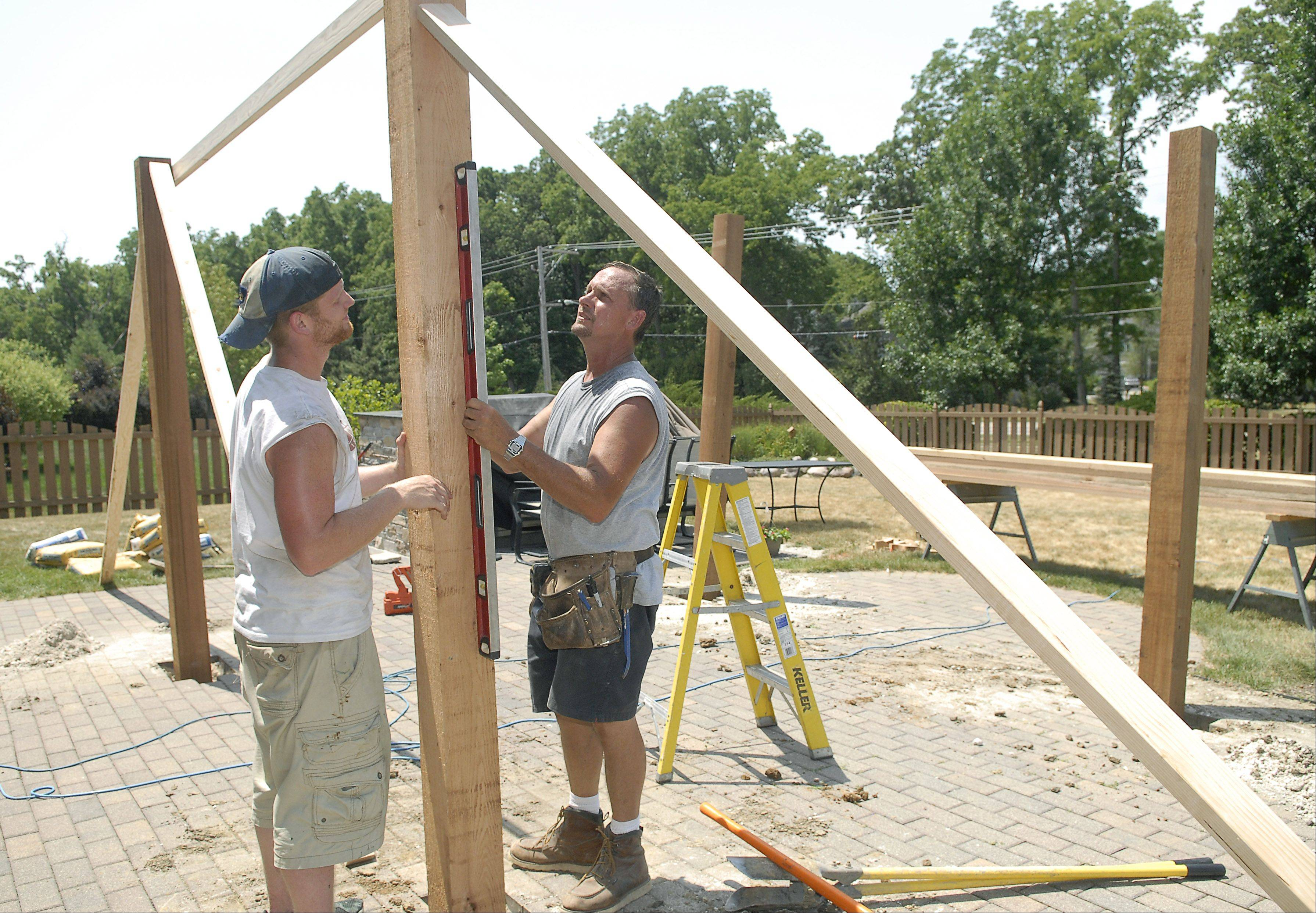 "Joe Weston, owner of JW Construction out of Lake Geneva, WI, and employee Max Hanna work on installing a pergola in the back yard of a Carpentersville home on Thursday, July 5. Weston likes to start early in order end early on hot days like this. He finds the extreme heat easier to deal with than extreme cold. ""The heat's easier to deal with. You can take a lot of breaks."" They manage the heat and are able to continue working in it by taking several water breaks in the shade. Hanna was ok in the heat as well saying, ""Starting early makes you feel better."" He jokingly added the heat makes for, ""Easy weight loss."""