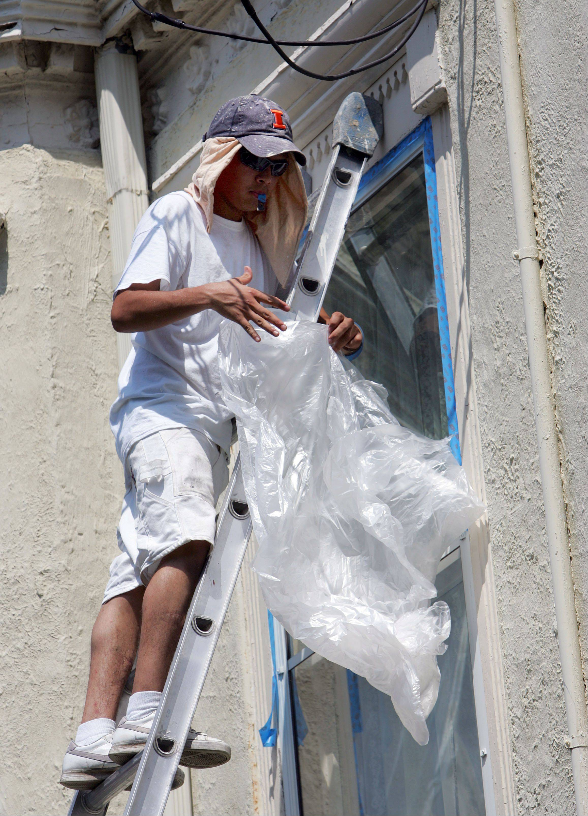 Painter Luis Lopez of DiVinci Painters preps the windows on Cook Mansion in downtown Libertyville .