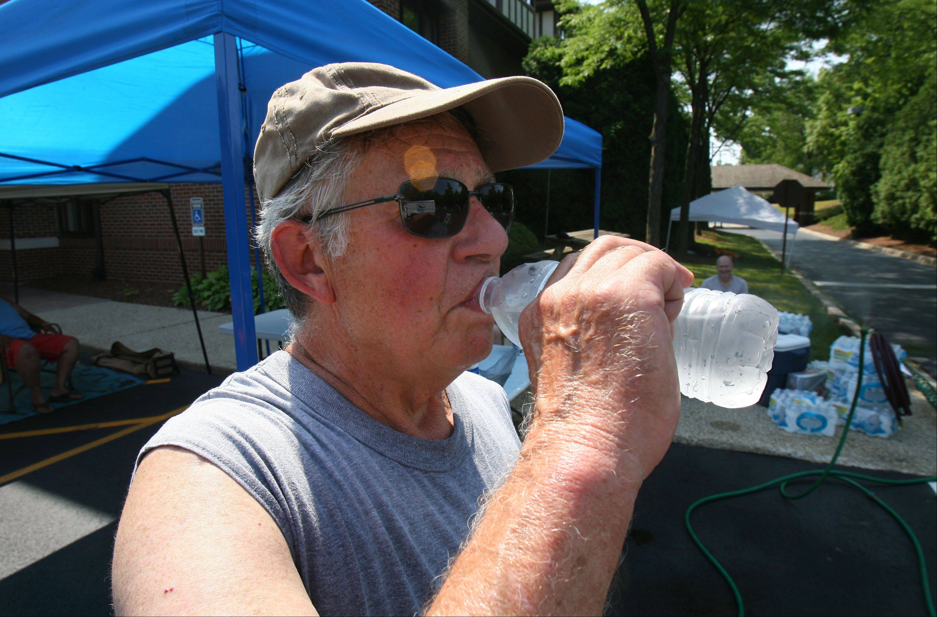 Bob Miller of Elk Grove takes a water break after setting up for the Dog Days event Thursday in downtown Libertyvile.