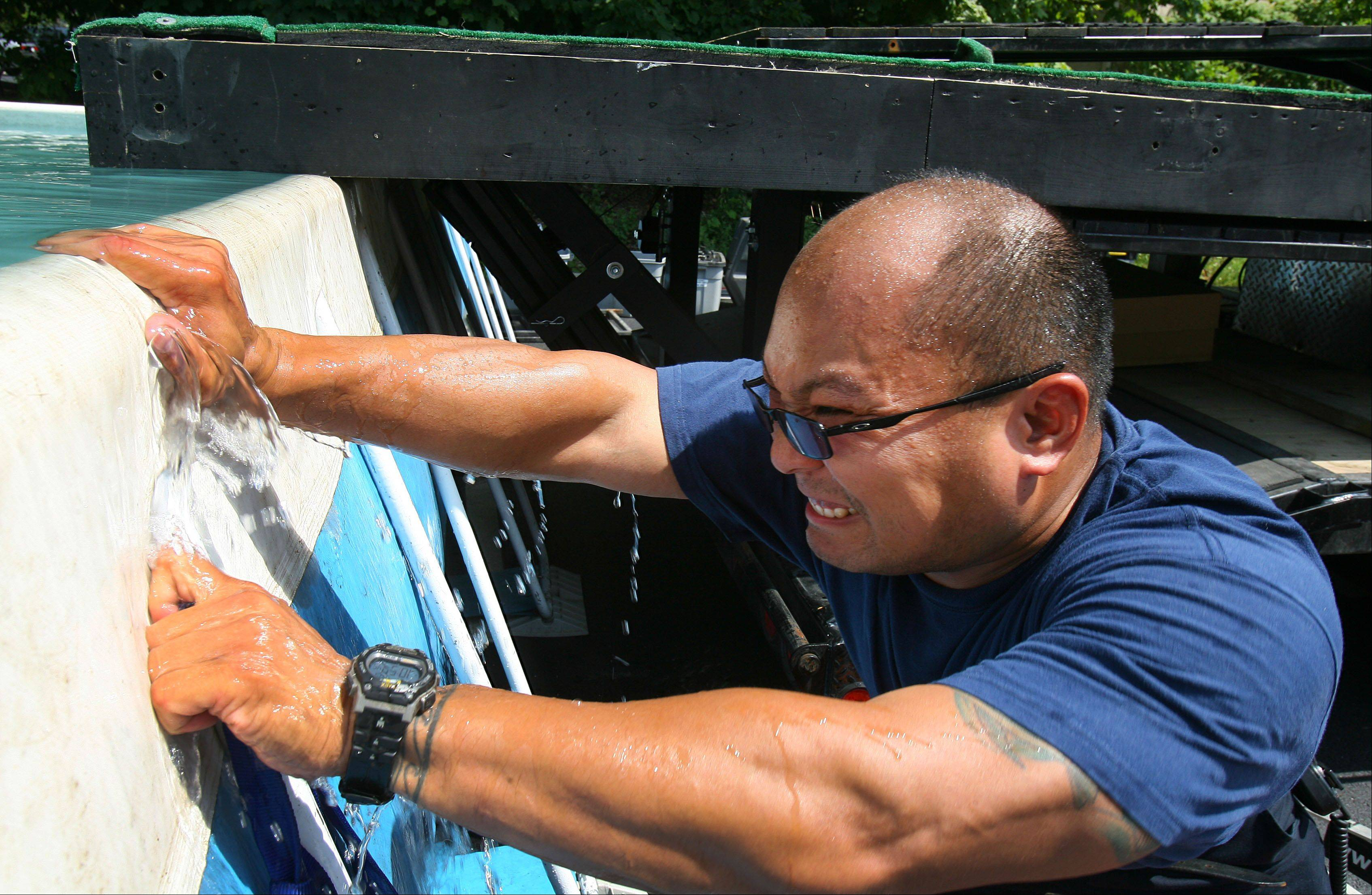 Libertyville firefighter Derek Kwong works on filling a dog jumping pool in preparation for the Dog Days event in downtown Libertyville.