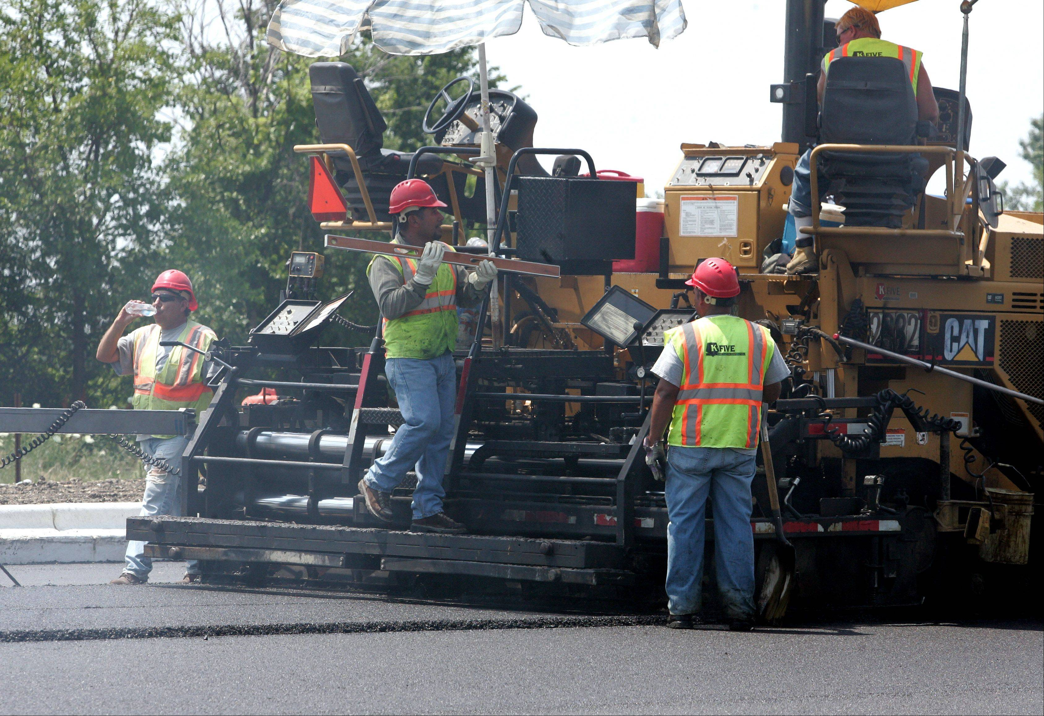 Crews deal with the heat as they work behind a paver on Butterfield Road in Wheaton on Thursday.
