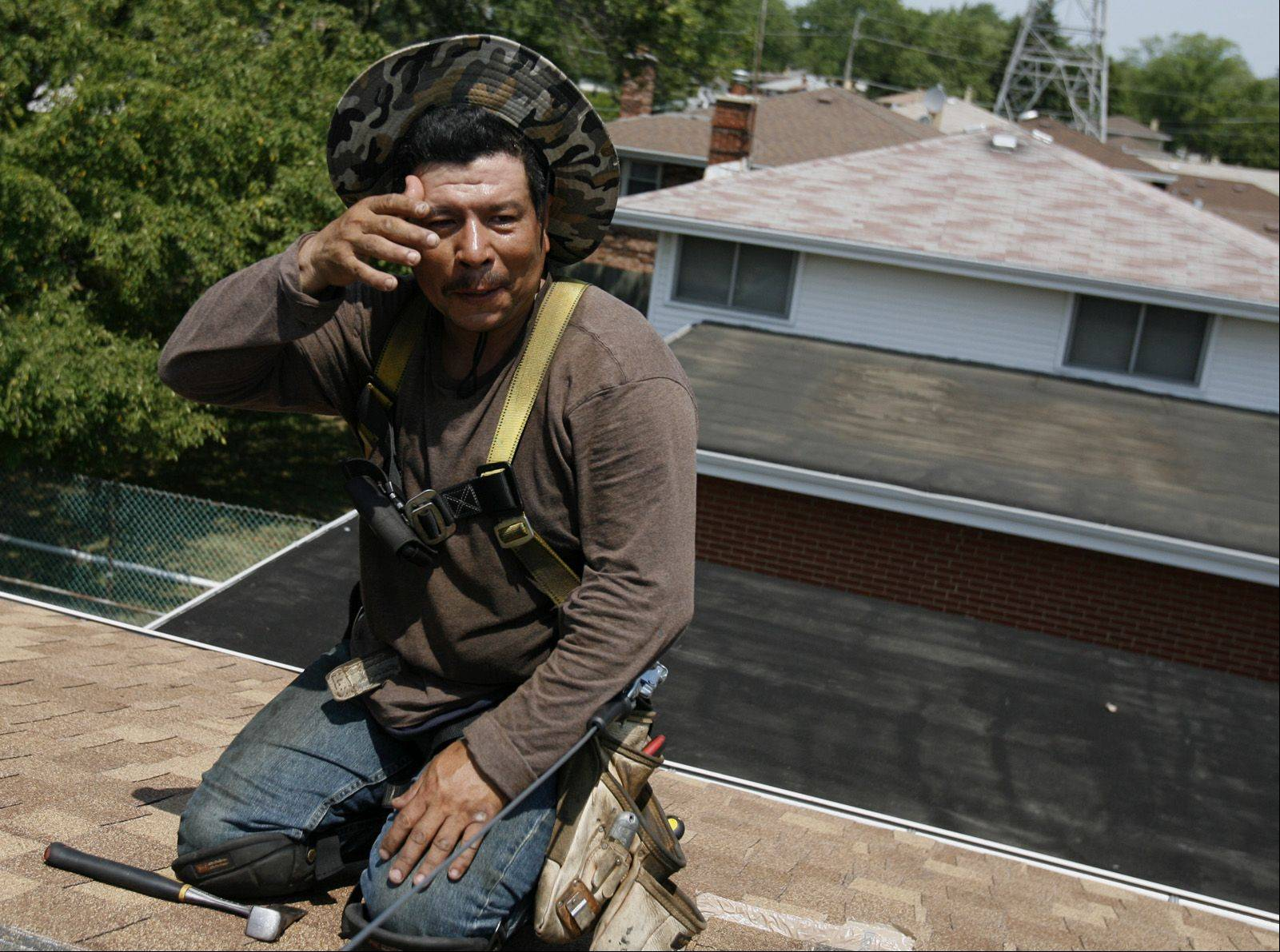 Armando Garcia with Lindholm Roofing swipes sweat away while working on a roof in Des Plaines on Thursday.