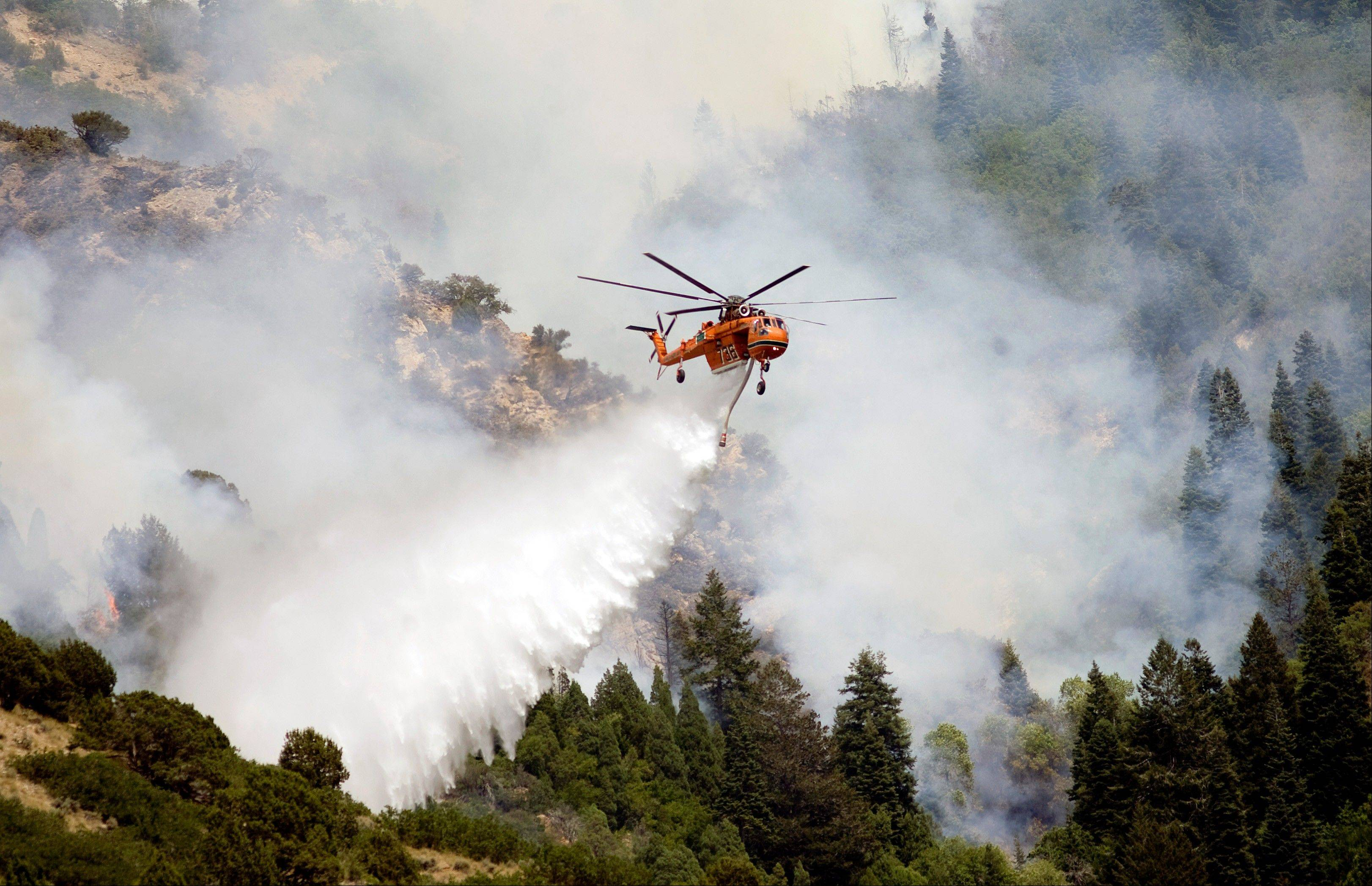Air crews continue to battle a wildfire near Alpine, Utah, Wednesday. The fire has charred 2,887 acres since it started Tuesday afternoon. About 500 homes will remain evacuated for at least two days.
