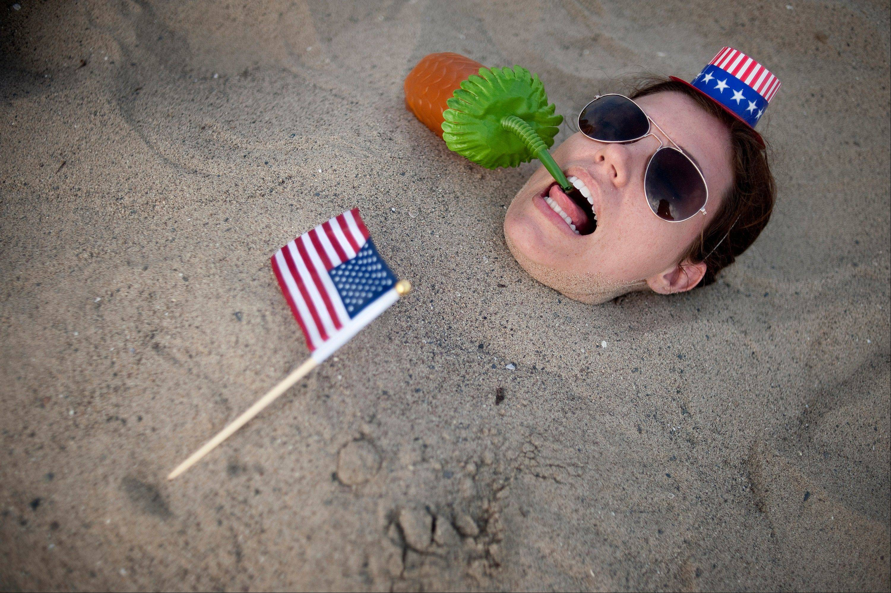 Alison Turner struggles for her straw after being buried by friends on Santa Monica Beach in Santa Monica, Calif., on Wednesday, July 4, 2012.