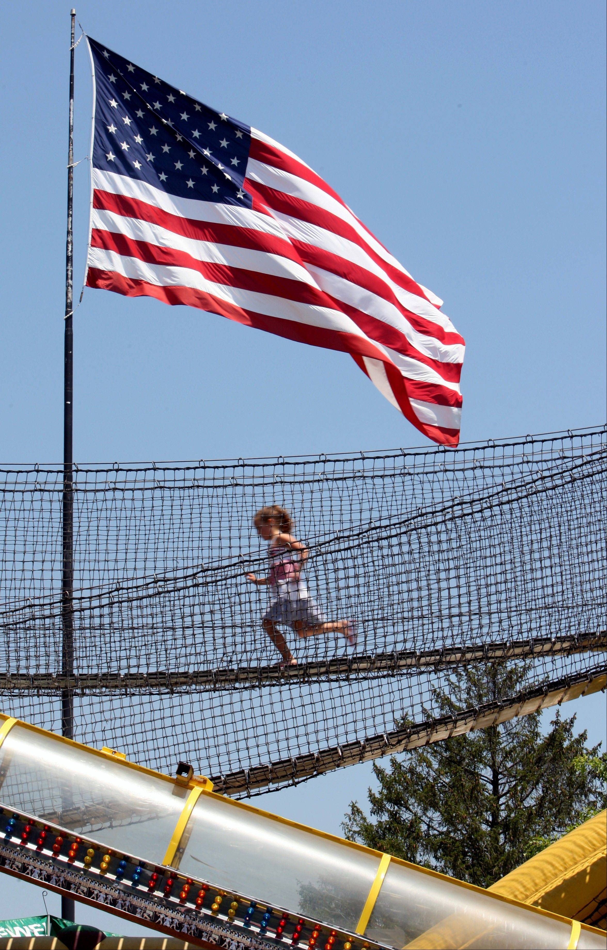 A young girl runs across a suspension bridge on a carnival ride at the Good Neighbor Day annual July Fourth celebration in Downingtown, Pa. on Wednesday July 4, 2012.