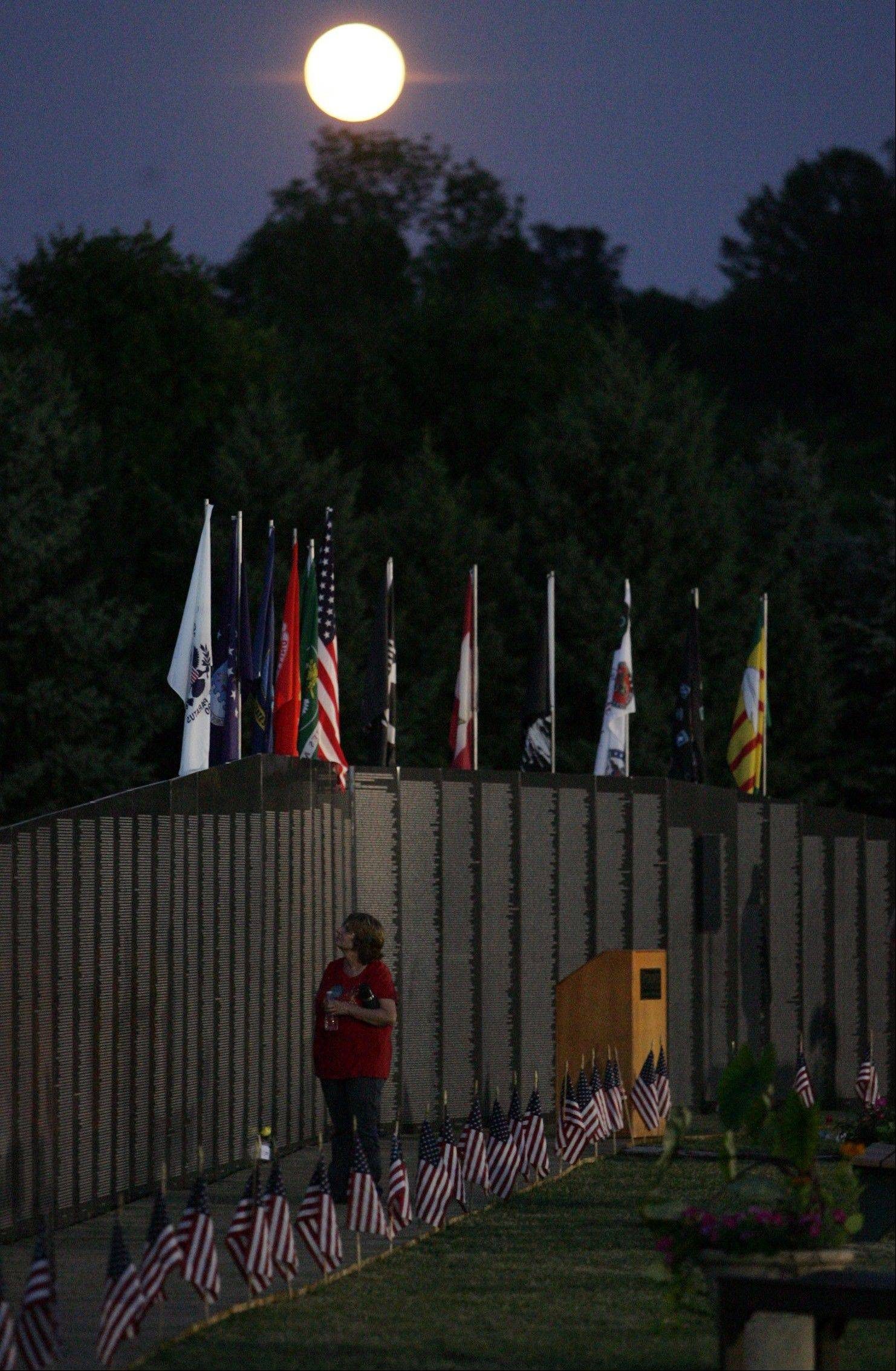 In this Tuesday, July 3, 2012, photo, a visitor looks at the names on The American Veterans Traveling Tribute Vietnam Memorial Wall at Purdue North Central in Westville, Ind. (