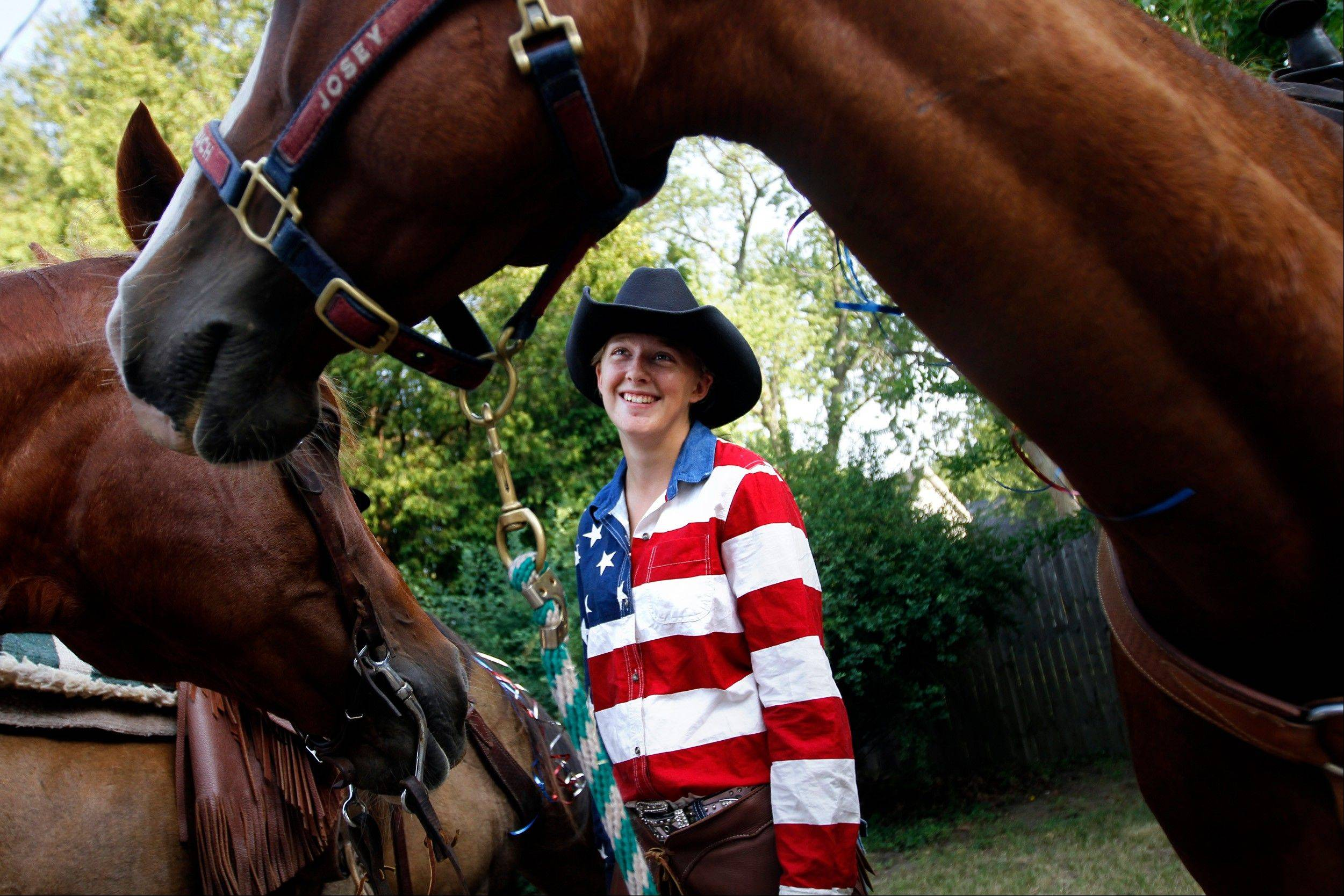 Kristen Willingham, 19, smiles at one of the horses from the Double JJ Ranch shortly before the beginning of the Fourth of July parade Wednesday, July 4, 2012 in Whitehall, Mich.