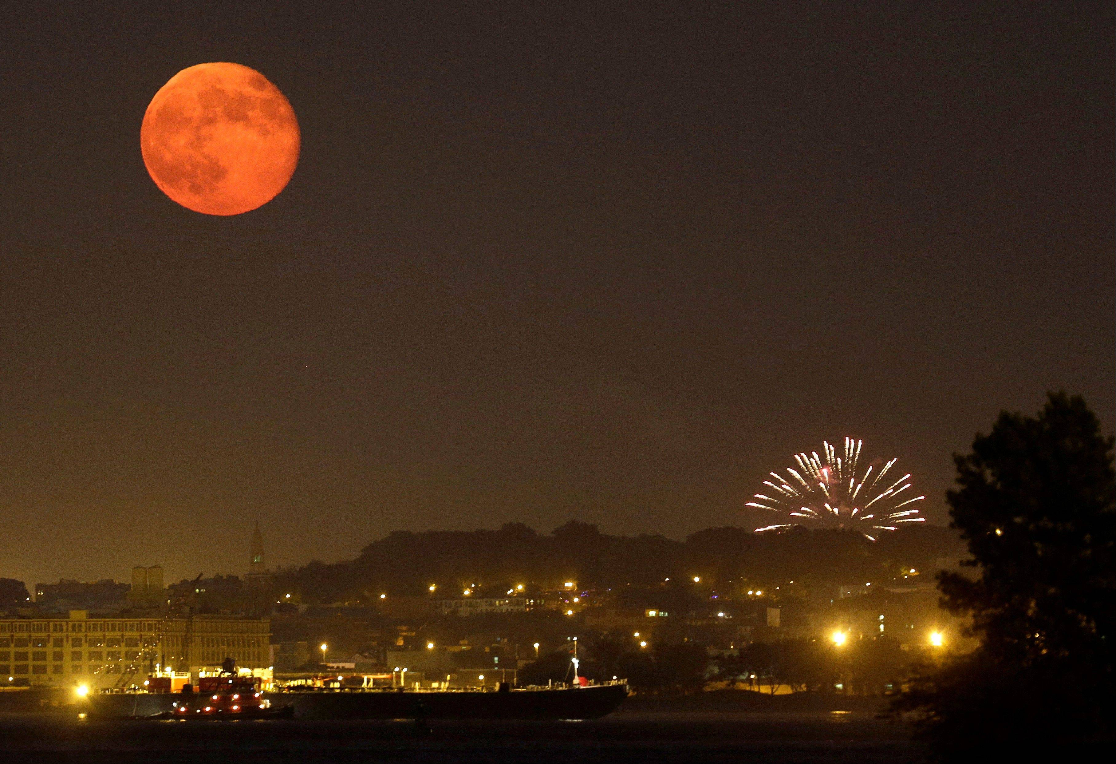 The full moon rises over Brooklyn as amateur fireworks explode are viewed from Bayonne, N.J., Wednesday, July 4, 2012.
