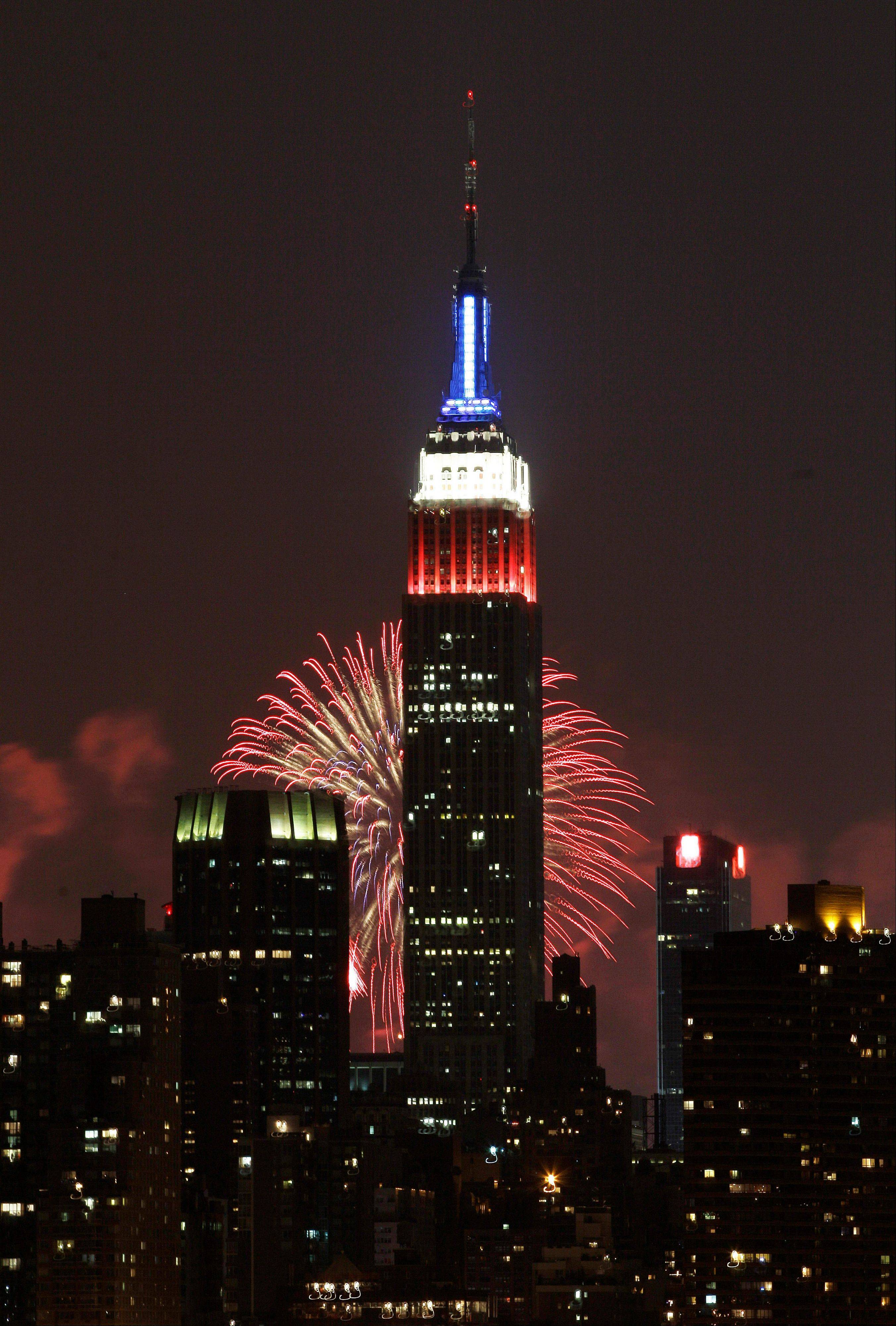 The Empire State Building, illuminated with red, white and blue lights, is seen from the Queens borough of New York, backlit by fireworks lighting up the sky over the Hudson River, during the Macy's Fourth of July fireworks show Wednesday, July 4, 2012, in New York.