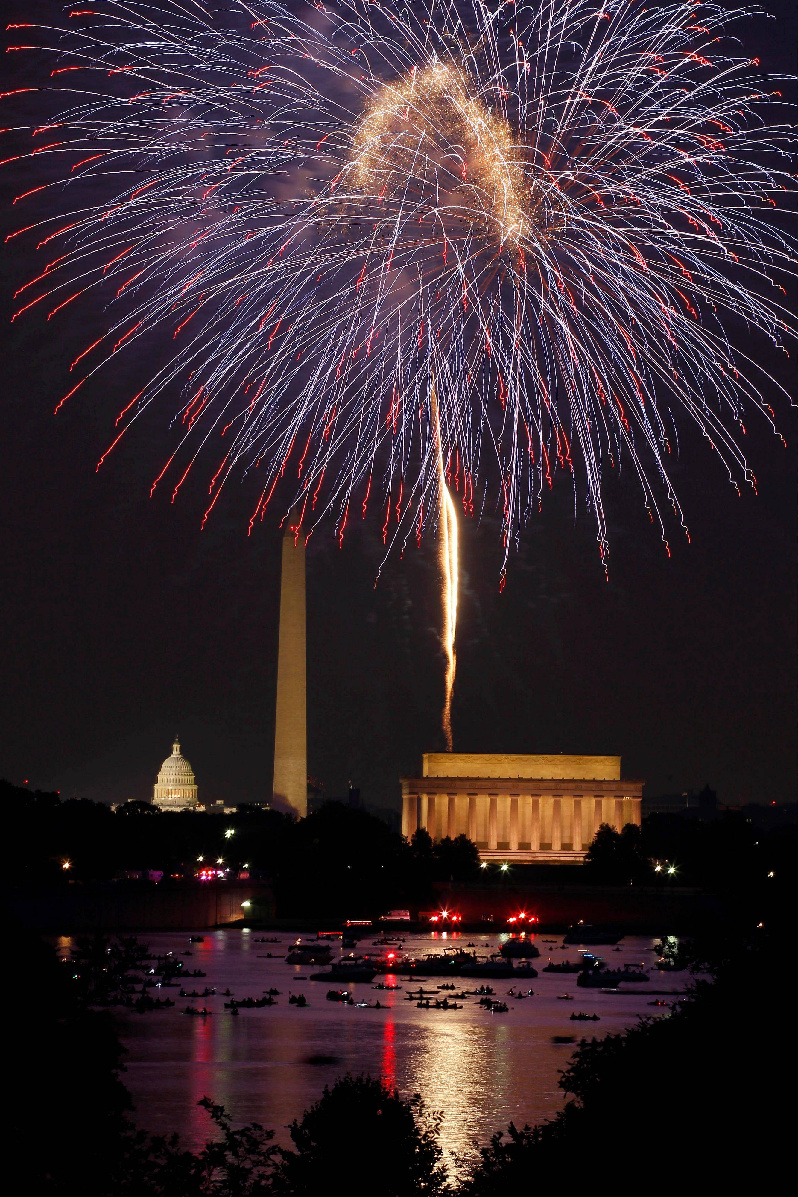 Fireworks light the sky over Washington and the U.S. Capitol, left, Washington Monument, and Lincoln Memorial, on Wednesday, July 4, 2012 in Arlington, Va.