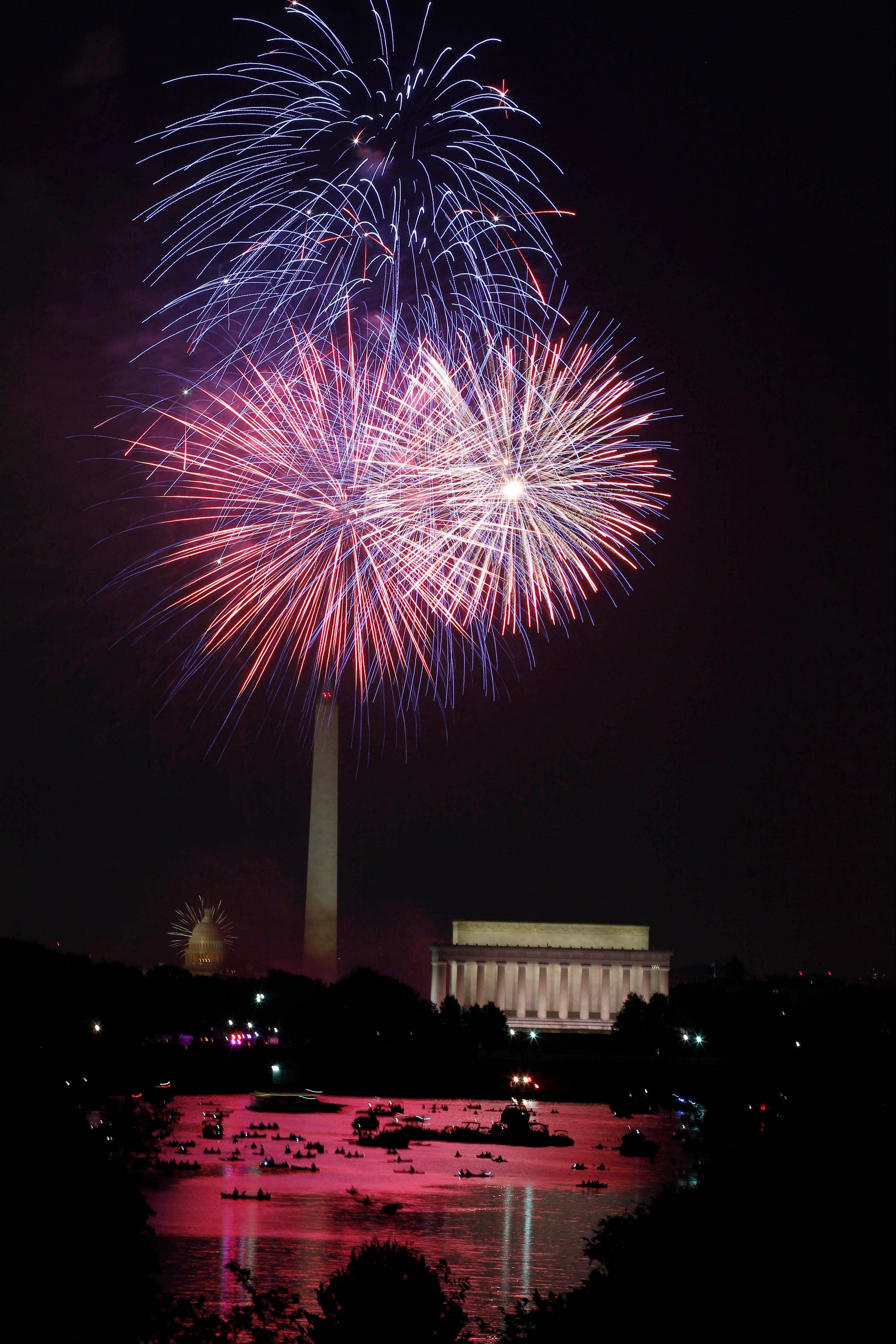 Fireworks light the sky over the U.S. Capitol, left, Washington Monument and Lincoln Memorial in Washington on Wednesday, July 4, 2012, as seen from Arlington, Va.
