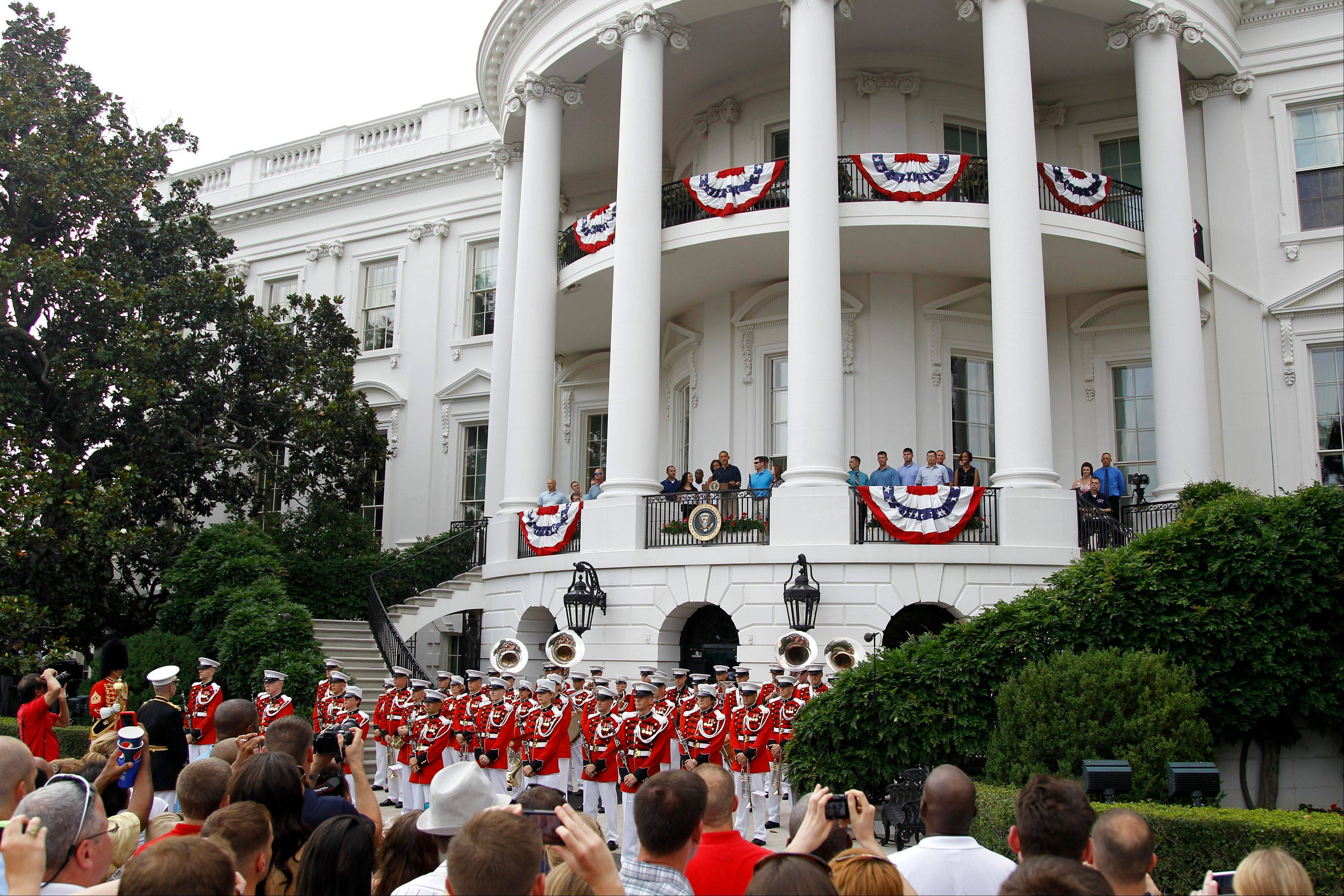 President Barack Obama speaks from the White House balcony as he and first lady Michelle Obama start an Independence Day celebration with a barbecue, concert and a view of fireworks, Wednesday, July 4, 2012, on the South Lawn of the White House in Washington.