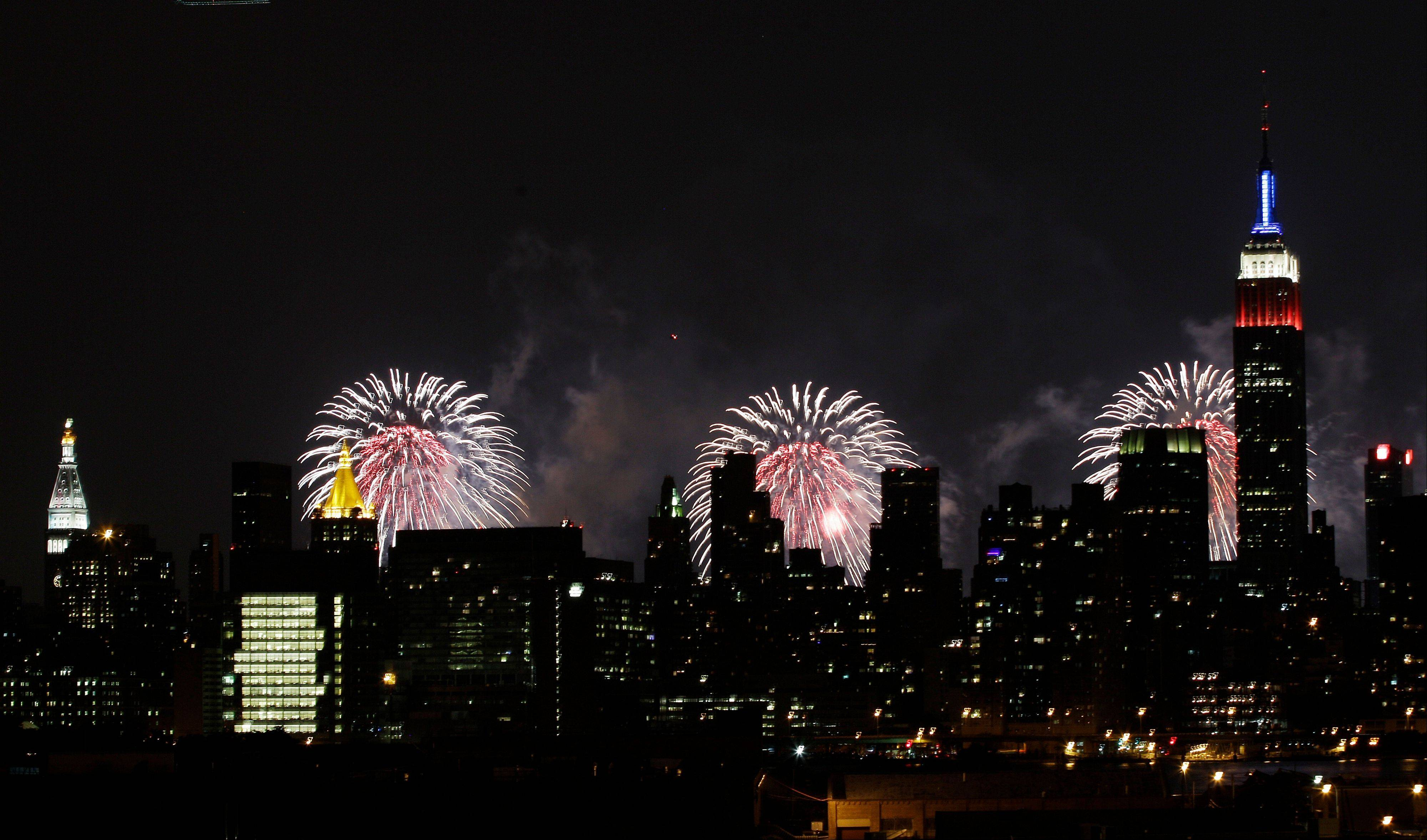 The Empire State Building, illuminated with red, white and blue lights, is seen from the Queens borough of New York, backlit by fireworks over the Hudson River, during the Macy's Fourth of July fireworks show Wednesday, July 4, 2012, in New York.