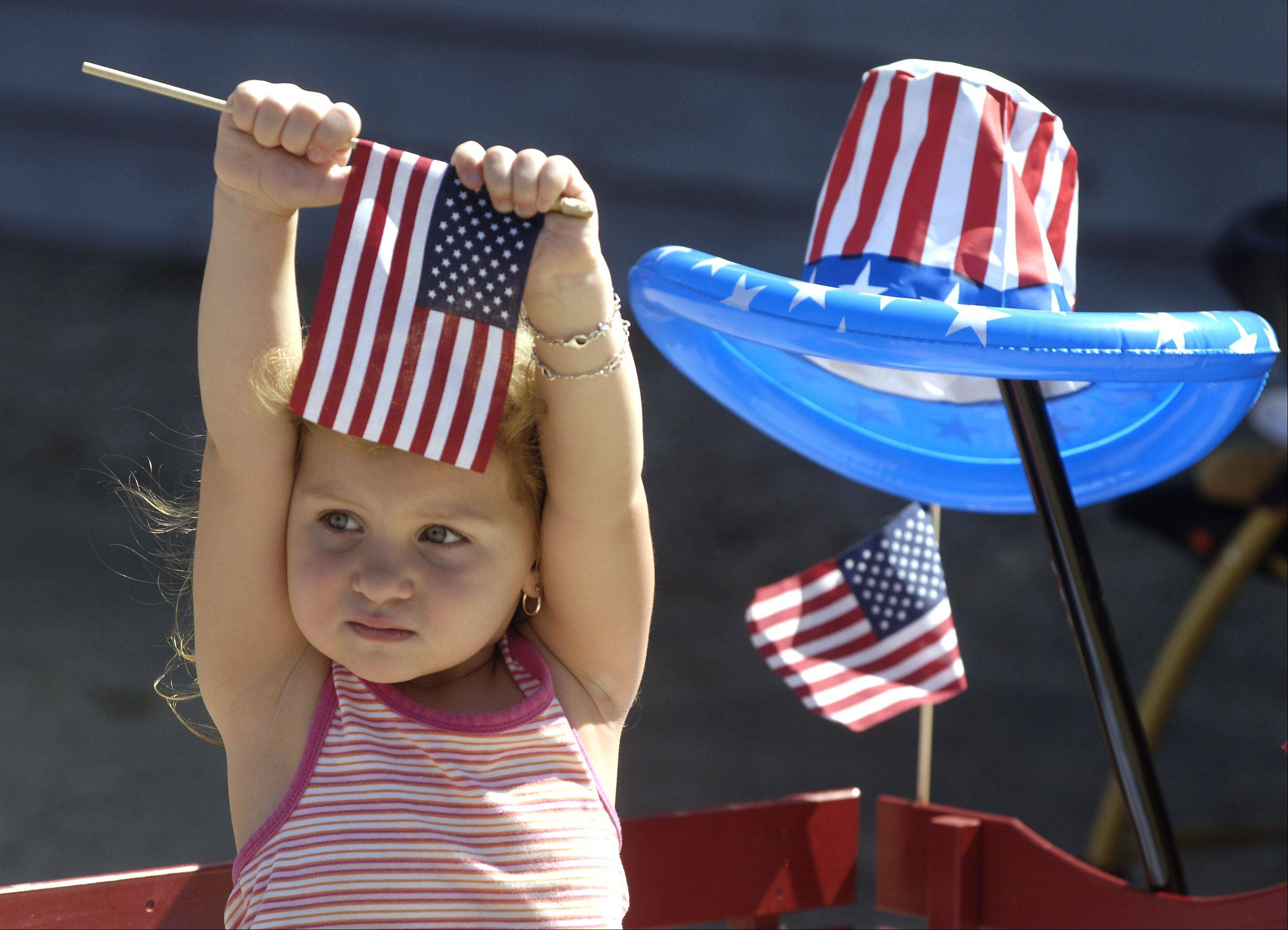 Czara Wicinski of Fox Lake, 3, is prepared for Independence Day with her flags and patriotic hat as she watches the Celebrate Fox Lake parade.