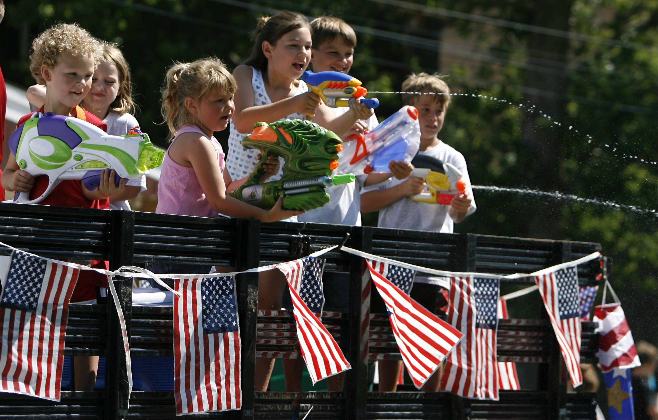 Children on the float from Superior Paving of Fox Lake cool off parade watchers.