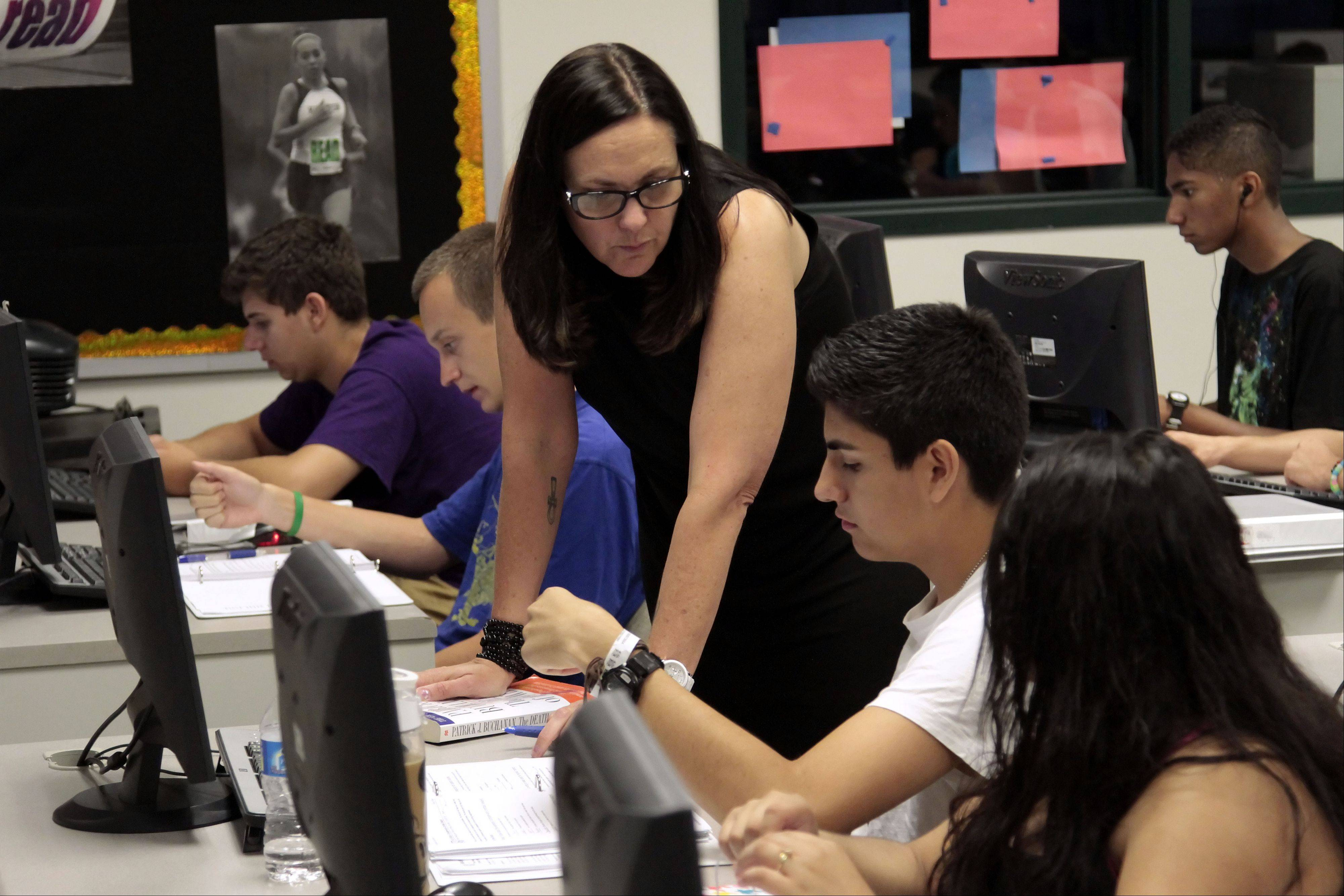 English teacher Tara Nieves helps 16-year-old Vernon Hills High School student Harold Torres with his assignment.
