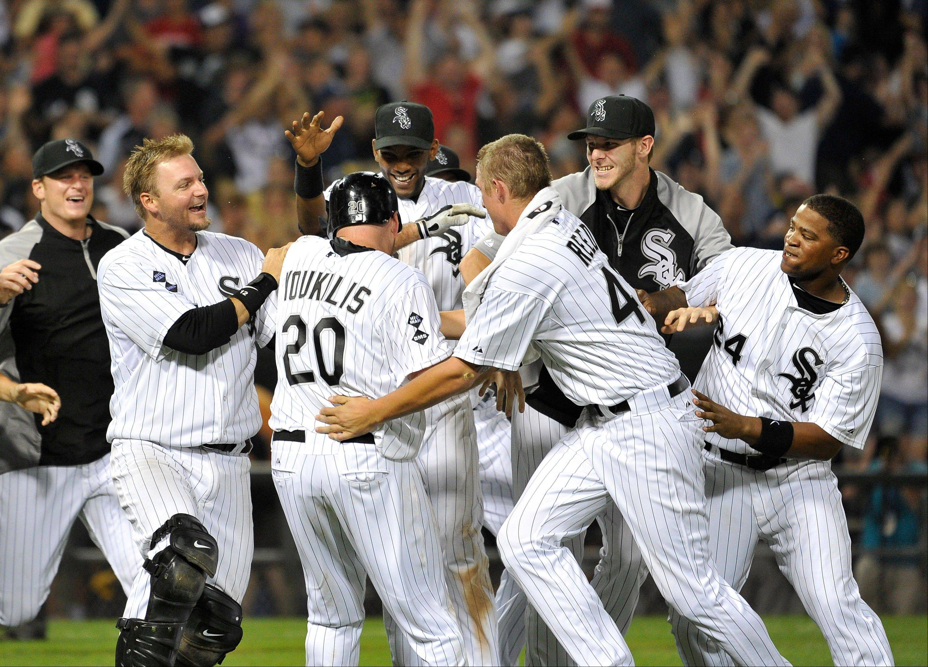 The White Sox' Kevin Youkilis, middle, is mobbed by teammates after hitting a game-winning single, scoring Alejandro De Aza in the 10th inning Wednesday night at U.S. Cellular Field.