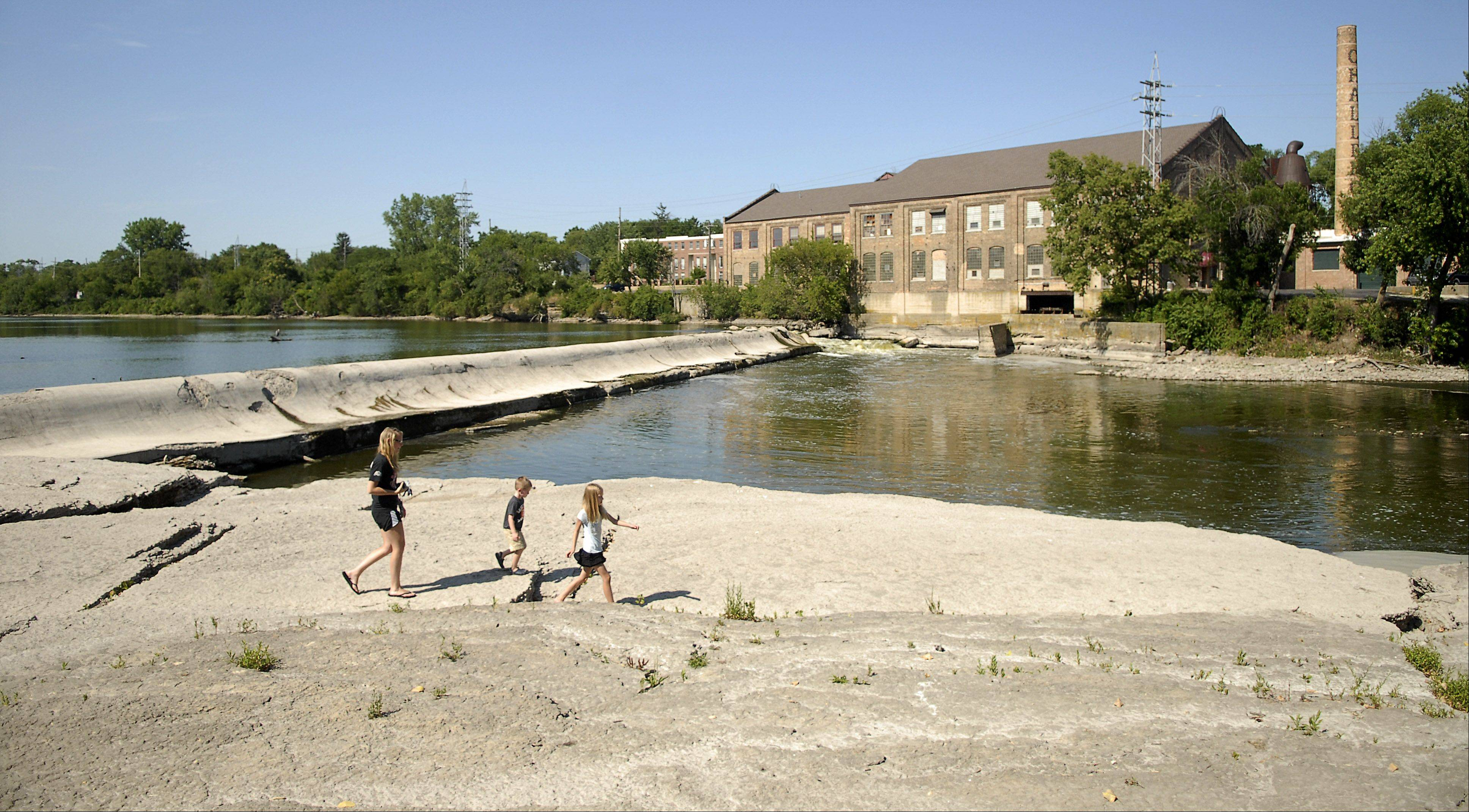 A family walks along an area that is normally under water near the Batavia dam along the Fox River. The area is parched due to the ongoing drought.