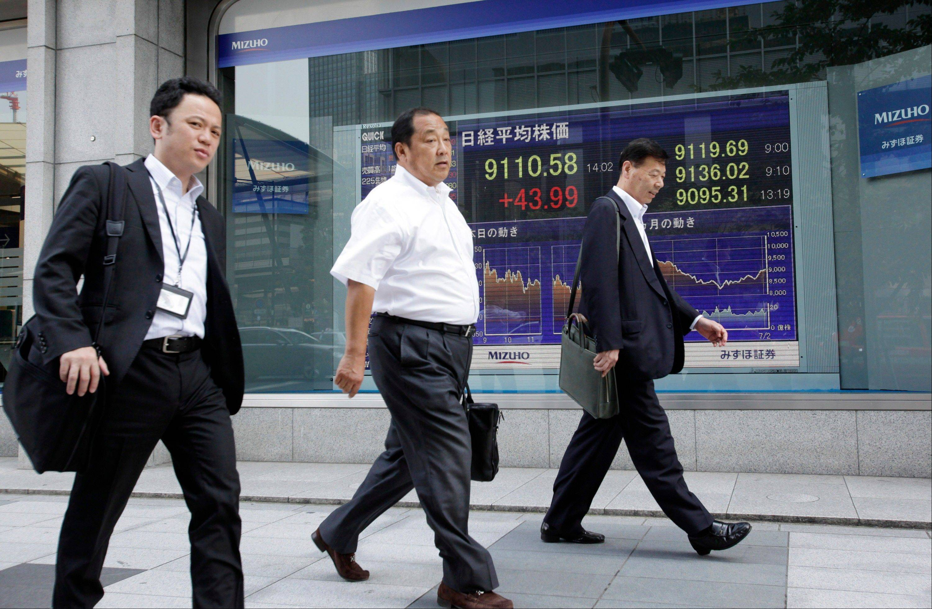 Office workers walk by the electric stock index display of a securities firm in Tokyo.