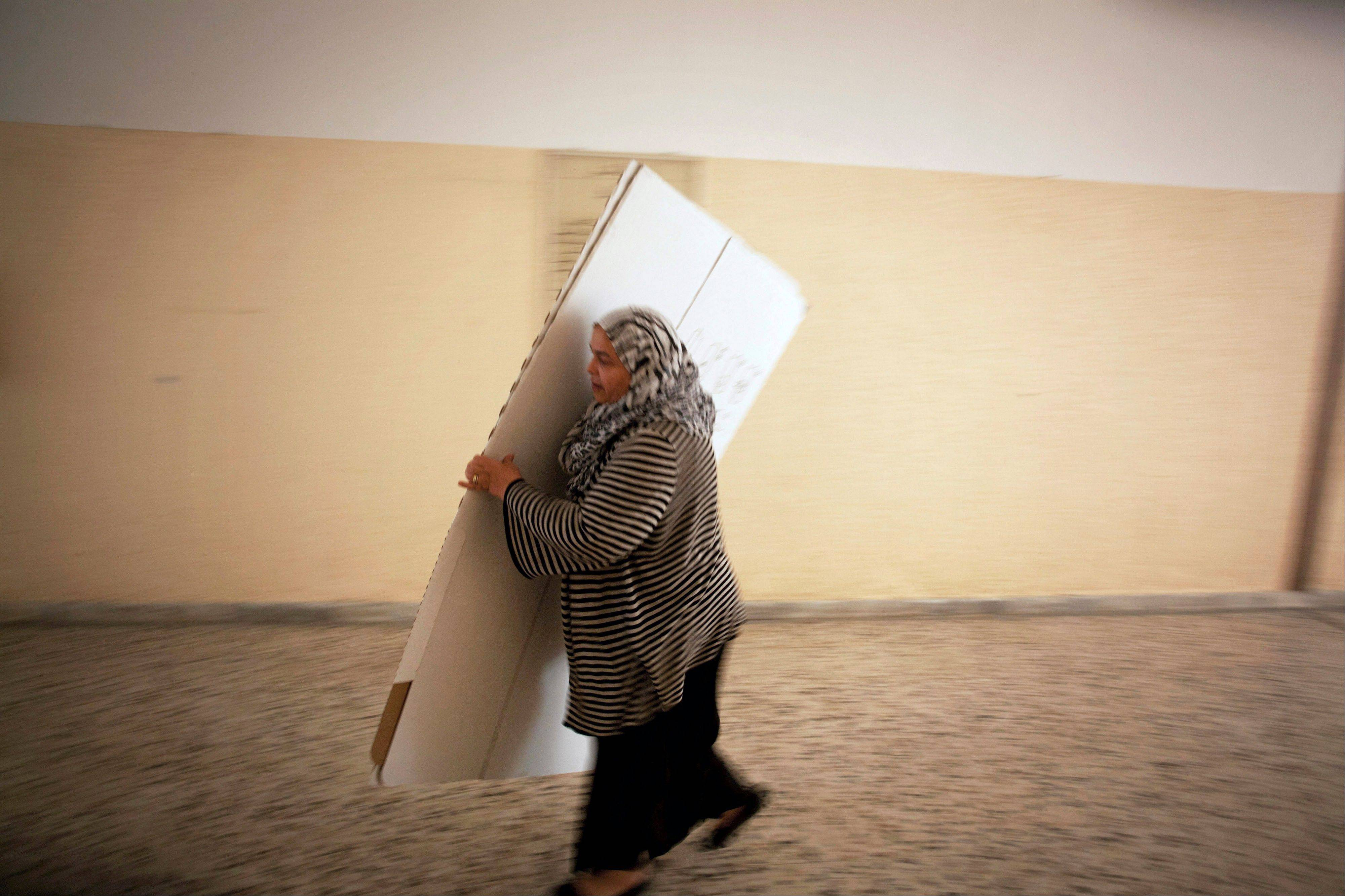 A Libyan election official works at a polling station Friday in Tripoli, Libya. The Libyan National Assembly elections — the first free election since 1969 — will take place Saturday.