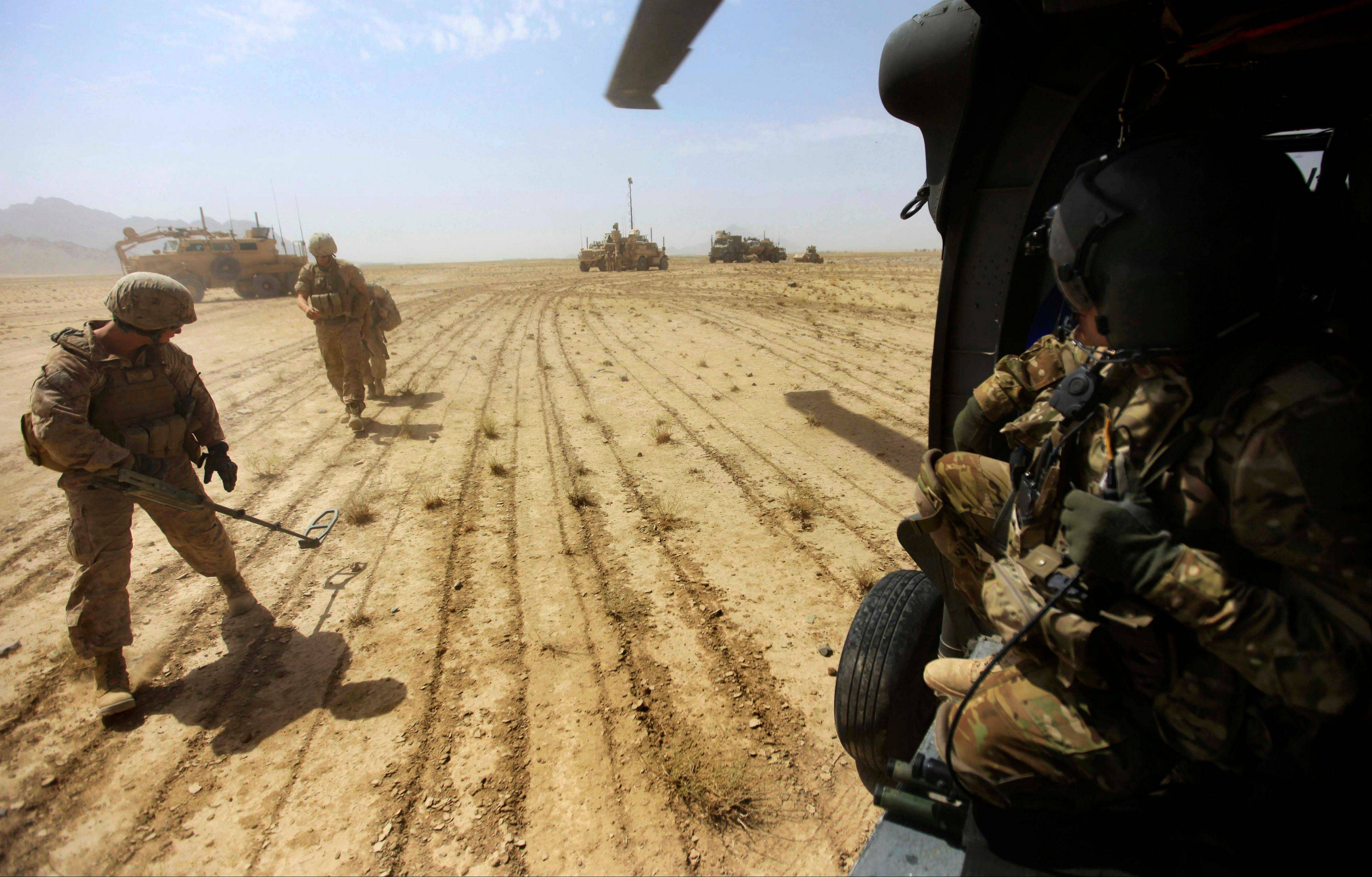 Associated Press/Sept. 7, 2011 U.S. Marines sweep for land mines in the Helmand Province of southern Afghanistan.