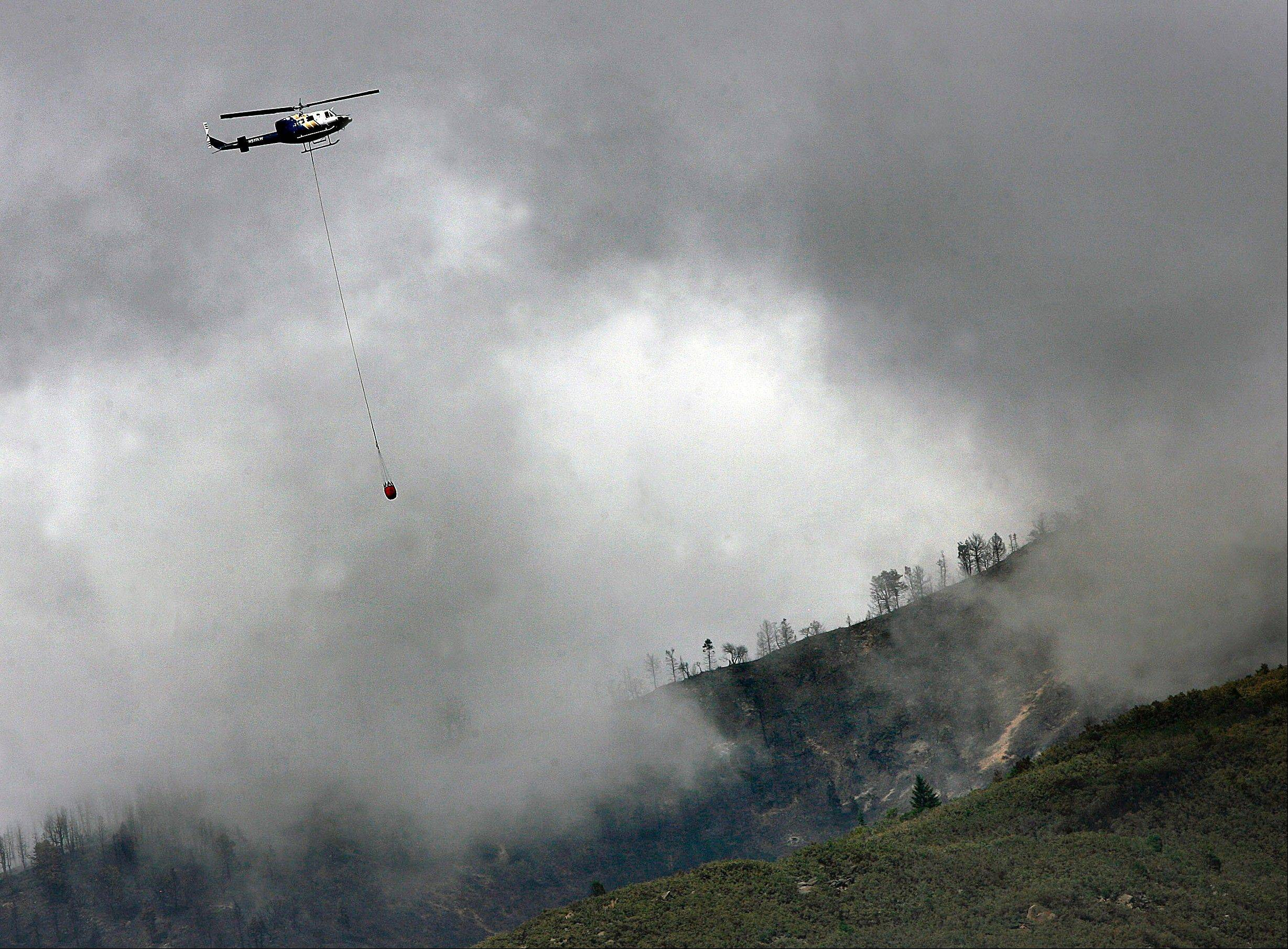 A helicopter drops water Thursday on hotspots of the Quail Fire near Alpine, Utah.