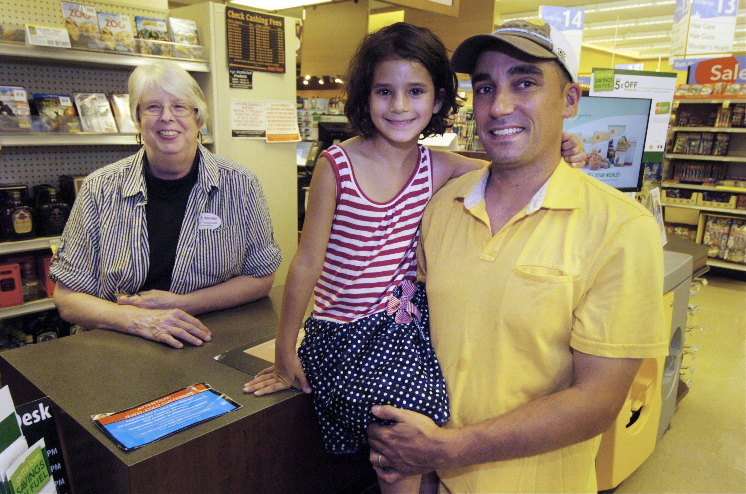 Chris Salituro and his daughter, Livia, with Service Manager Mary Kuehling, who held an envelope of money they had lost at the Vail Street Jewel in Arlington Heights.