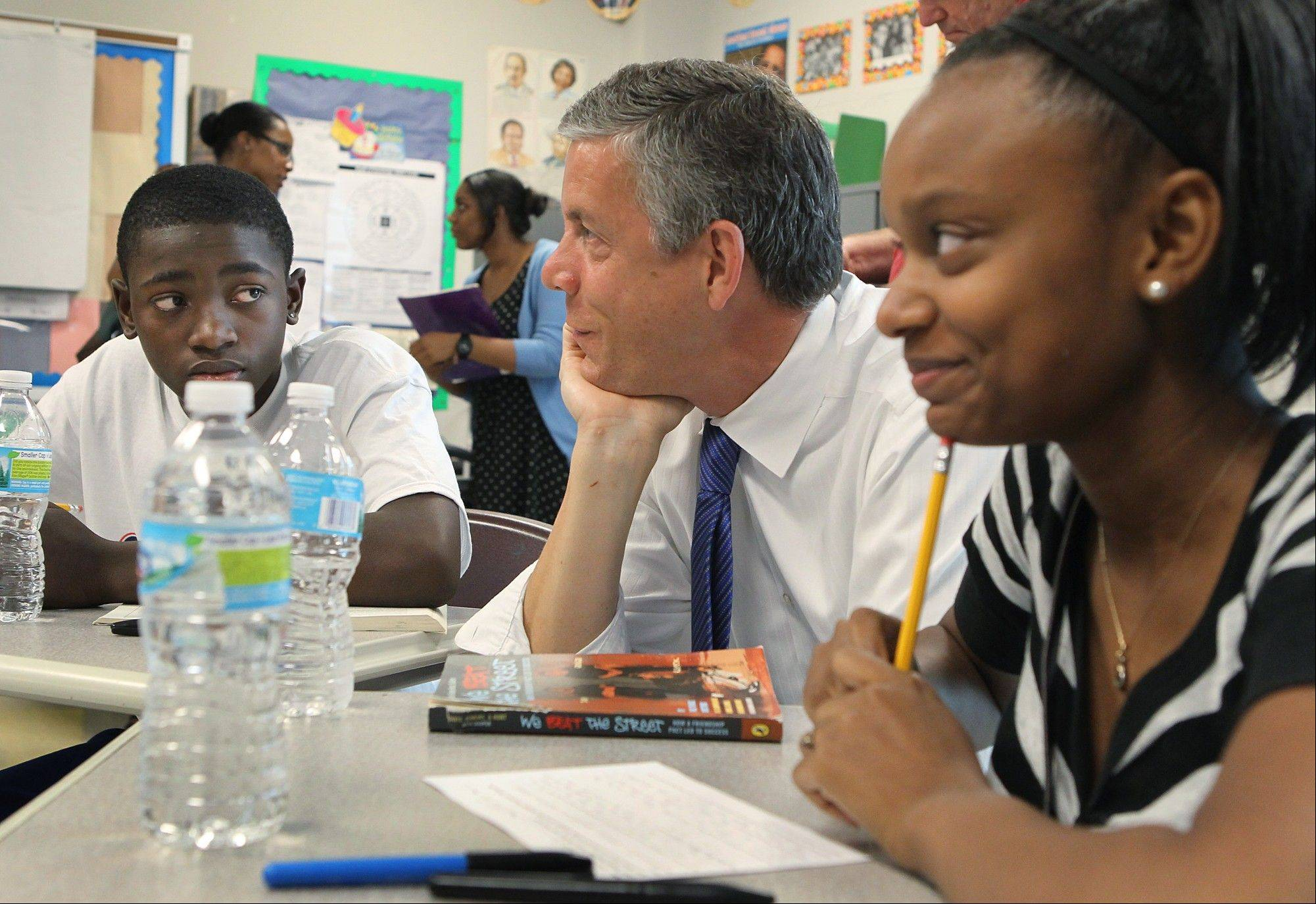 U.S. Secretary of Education Arne Duncan, center, visits with students in St. Louis. Two more states — Wisconsin and Washington — have been granted relief from key requirements of the Bush-era No Child Left Behind law.