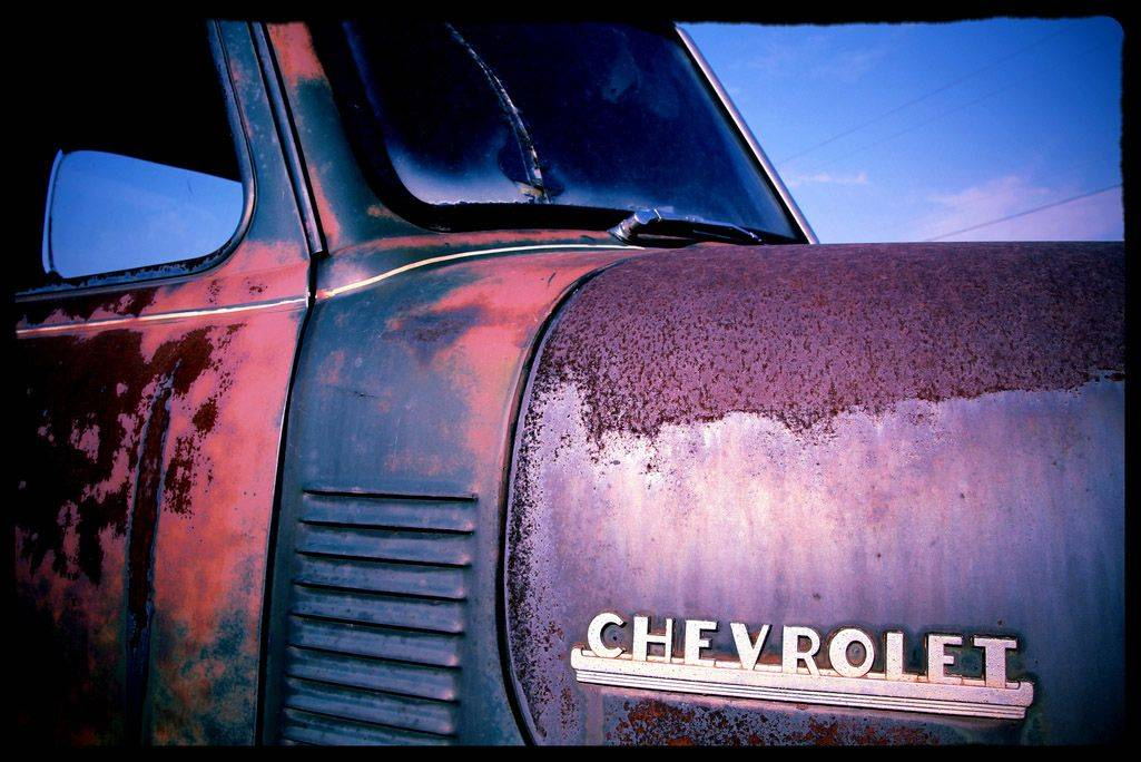 Seen along US 2 outside Minot, ND. This car is one of about 200 vintage cars for sale in an apparent junk yard. I took about 300 photos of 50 cars and liked this the best because of the colorization, the focus on the rust and the curves of this classic Chevrolet car.