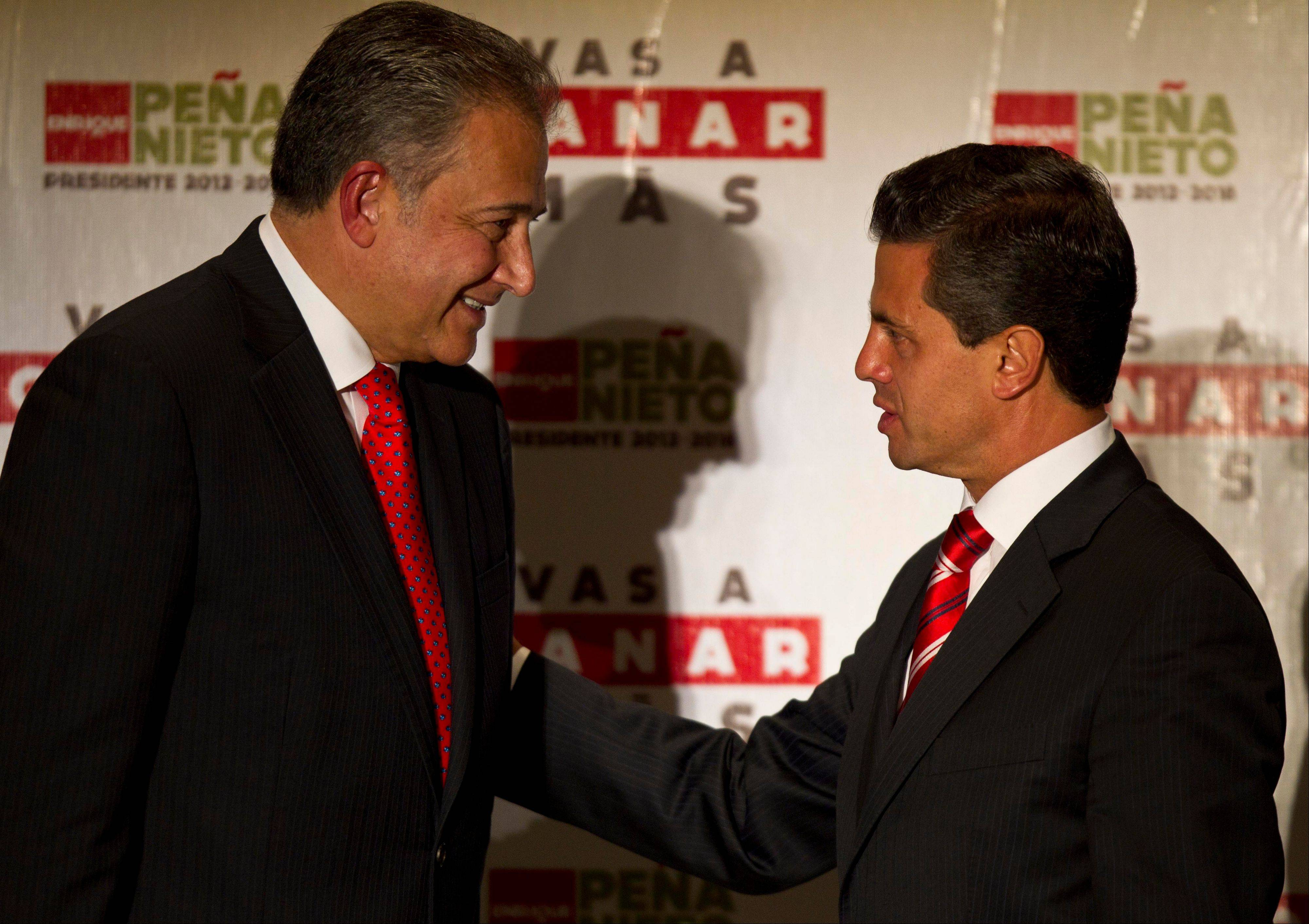 Associated Press/June 14, 2012Then presidential candidate Enrique Pena Nieto, right, of the Institutional Revolutionary Party, greets retired Colombian Gen. Oscar Naranjo during a press conference in Mexico City.
