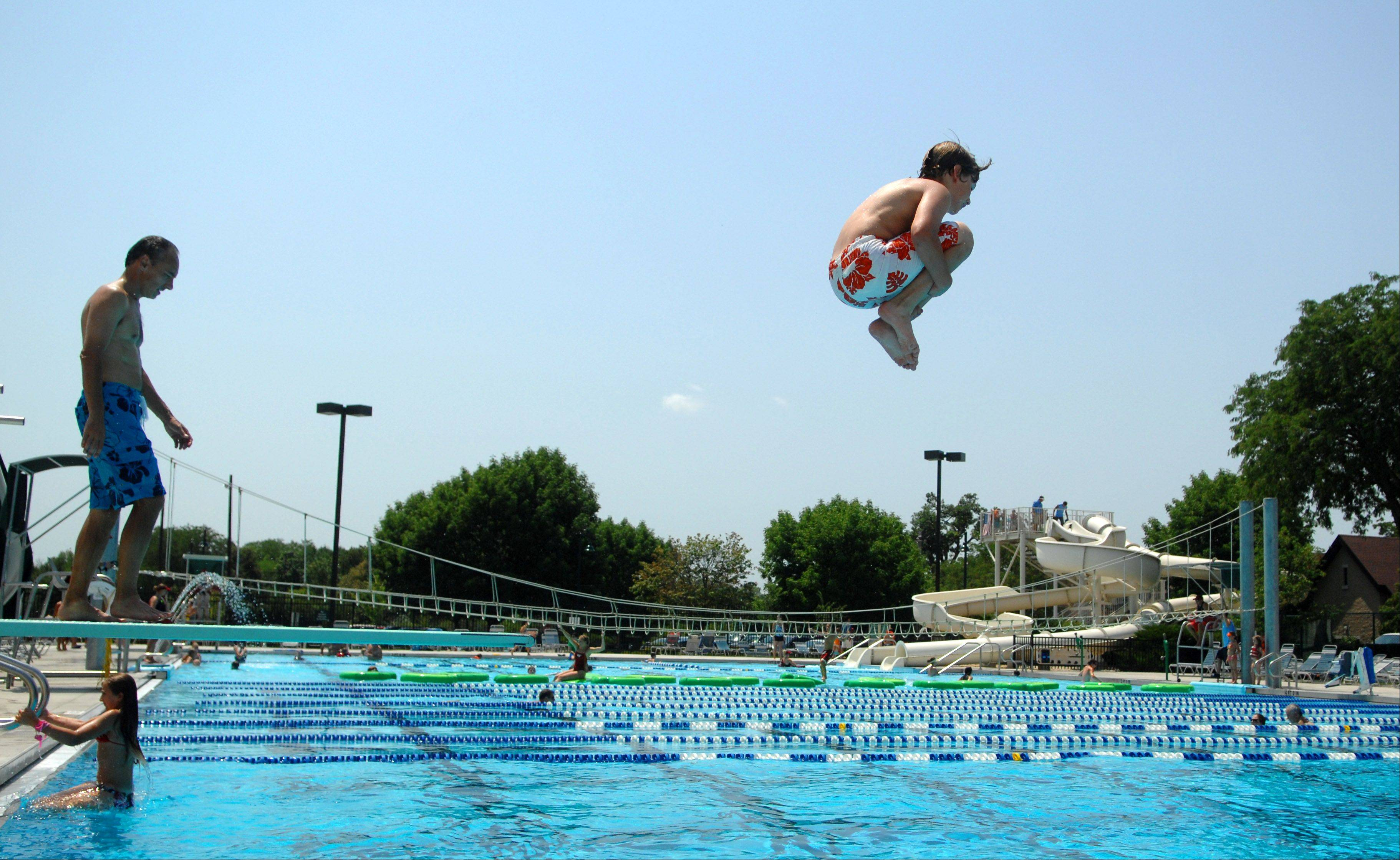 Connor Reece, 11, of St. Charles does a cannonball into Swanson Pool at Pottawatomie Park in St. Charles Friday. The pool had a line to get in when they opened for public swimming at noon.