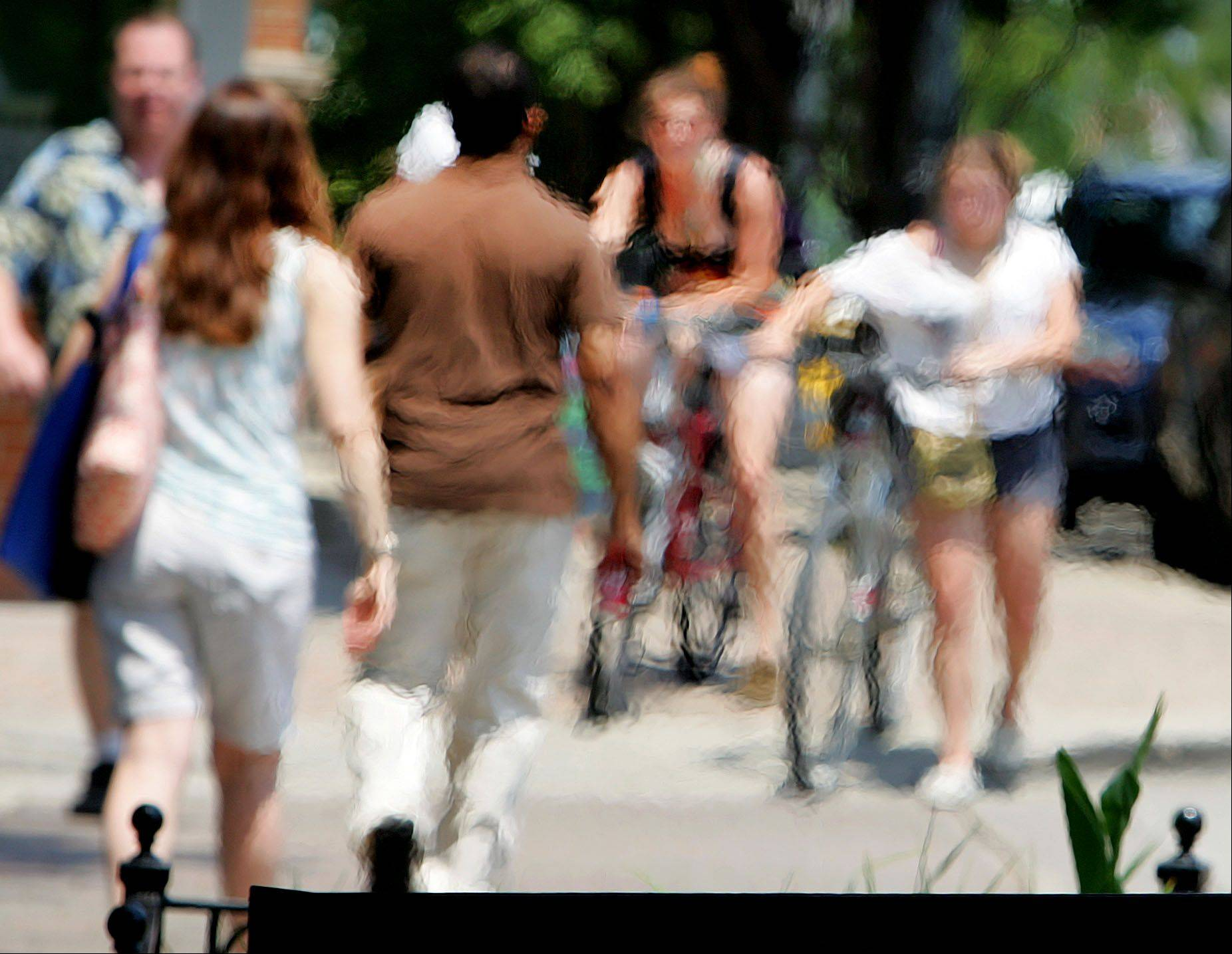 Heat distorts pedestrians as it rises off of food grilles during Mainstreet Libertyville's out to lunch in Cook Park.