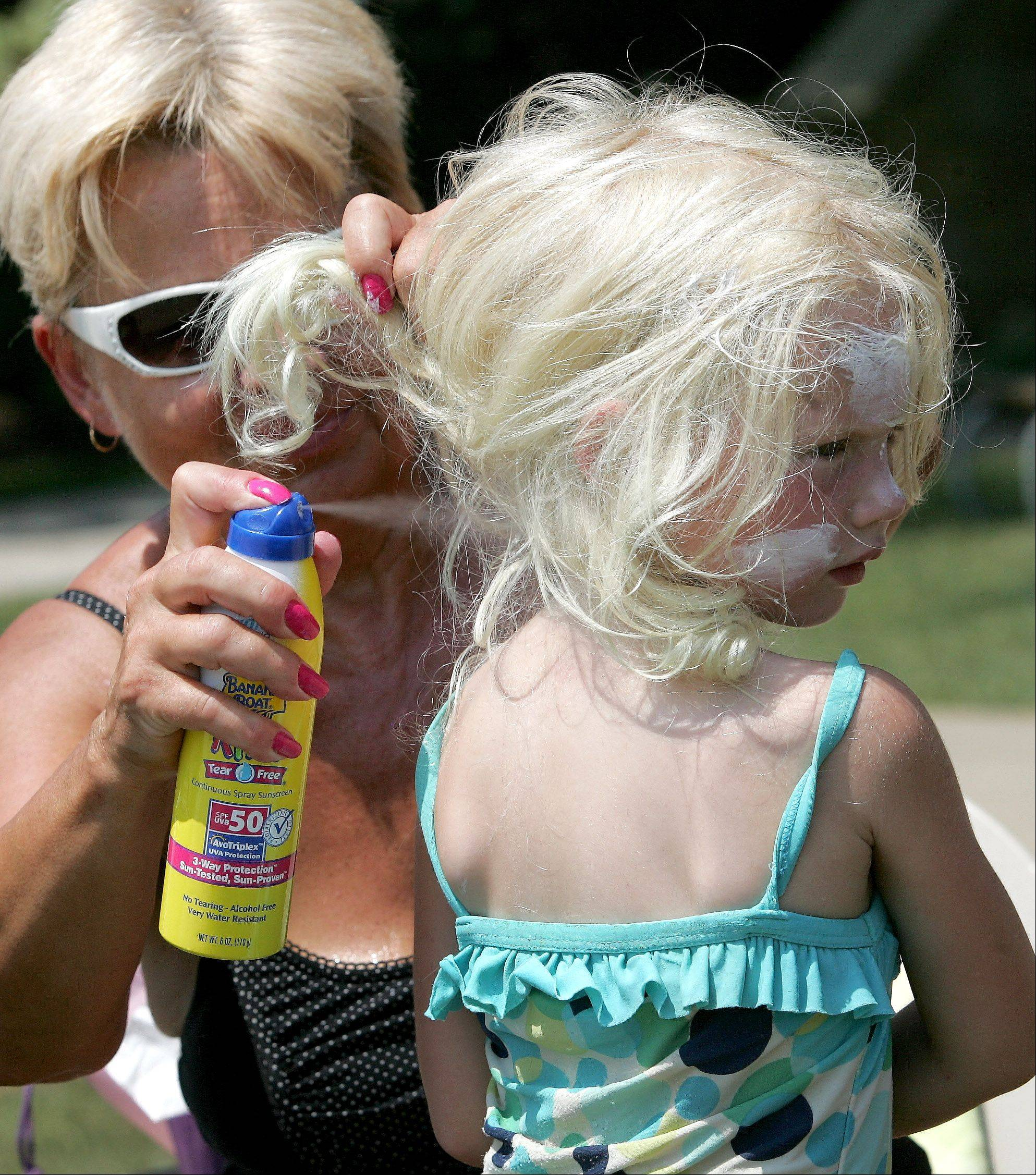 Hope Olin gives Addison Olin, 4, lots of sunscreen during an outing to Centennial Beach in Naperville.
