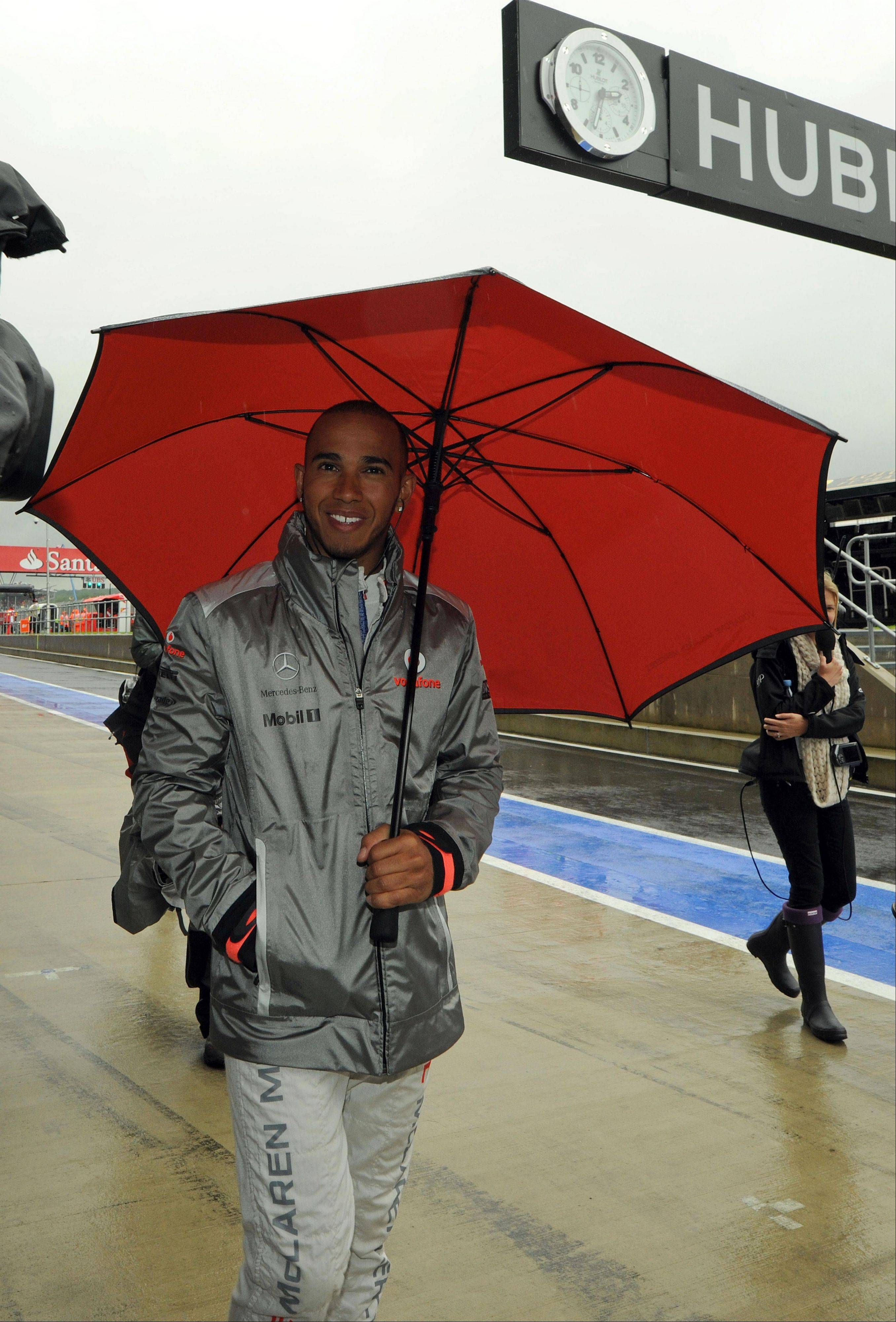 Britain's Lewis Hamilton, a McLaren-Mercedes Formula 1 car driver, smiles as he walks along pit lane Friday during practice at the Silverstone circuit, England.