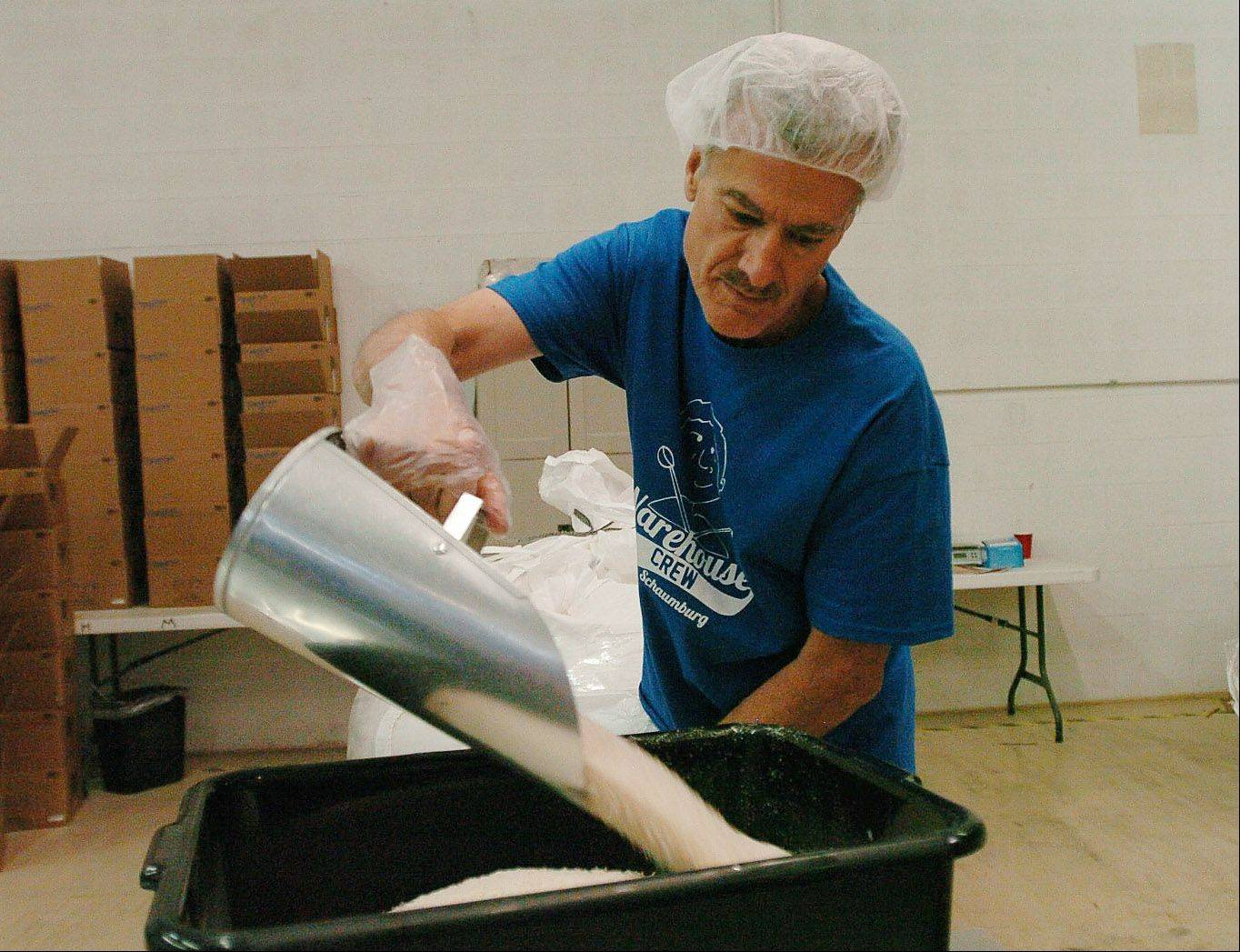 Rich Direnzo of Lombard fills a bin with rice at Feed My Starving Children in Schaumburg.