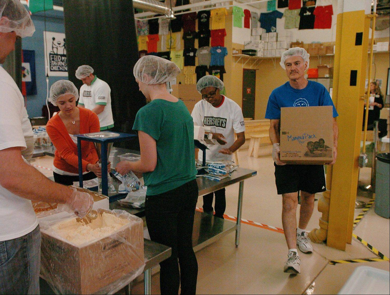 Rich takes away a freshly packed MannaPack box for shipping at Feed My Starving Children in Schaumburg.