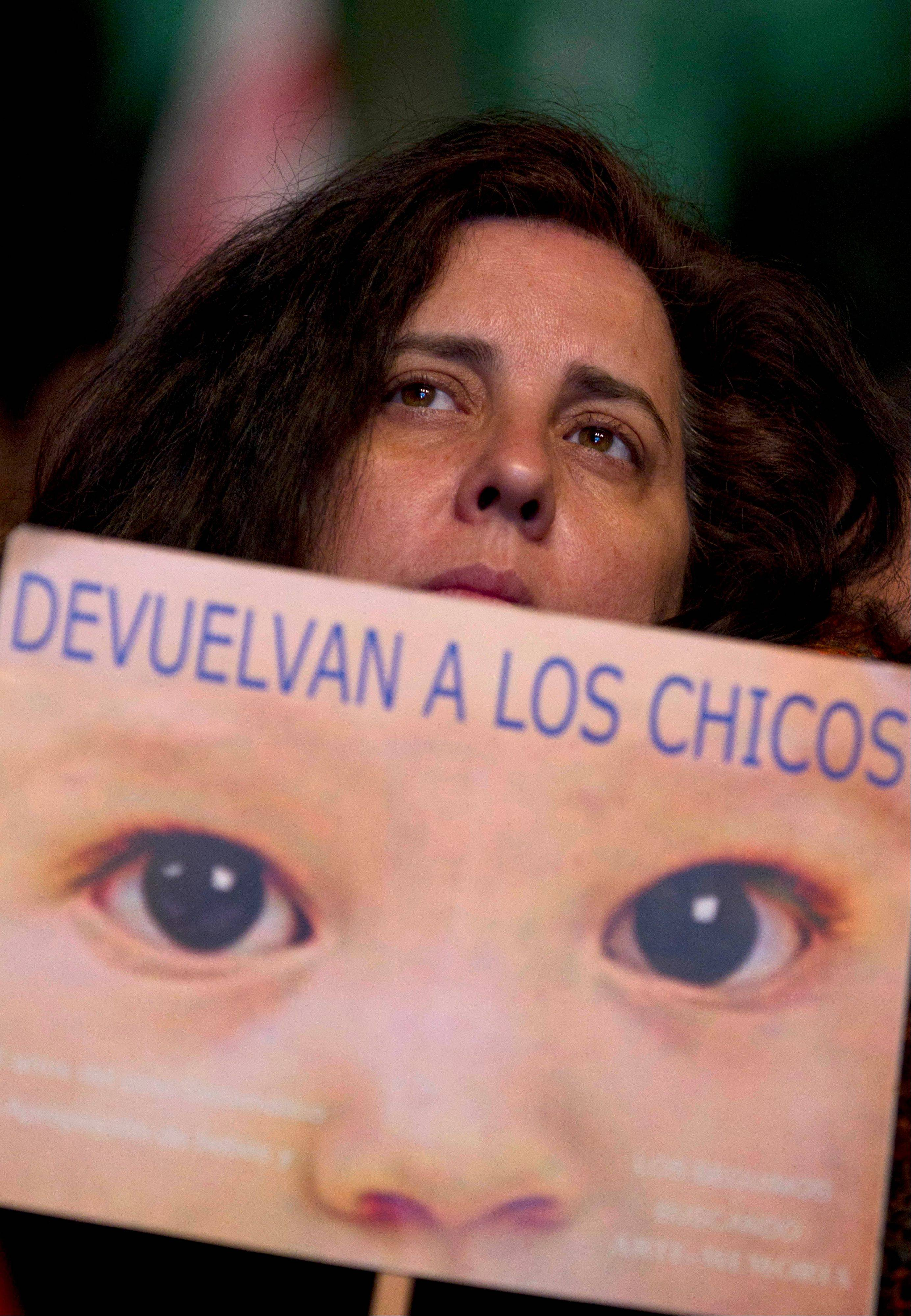 "A woman holds a sign that reads in Spanish ""Give the children back"" outside a court where Argentina's historic stolen babies trial is being held in Buenos Aires, Argentina, Thursday, July 5, 2012. Former dictators Jorge Videla and Reynaldo Bignone and a handful of other retired military and police officials are accused of systematically stealing babies from leftists who were kidnapped and killed when a military junta ran the country three decades ago."