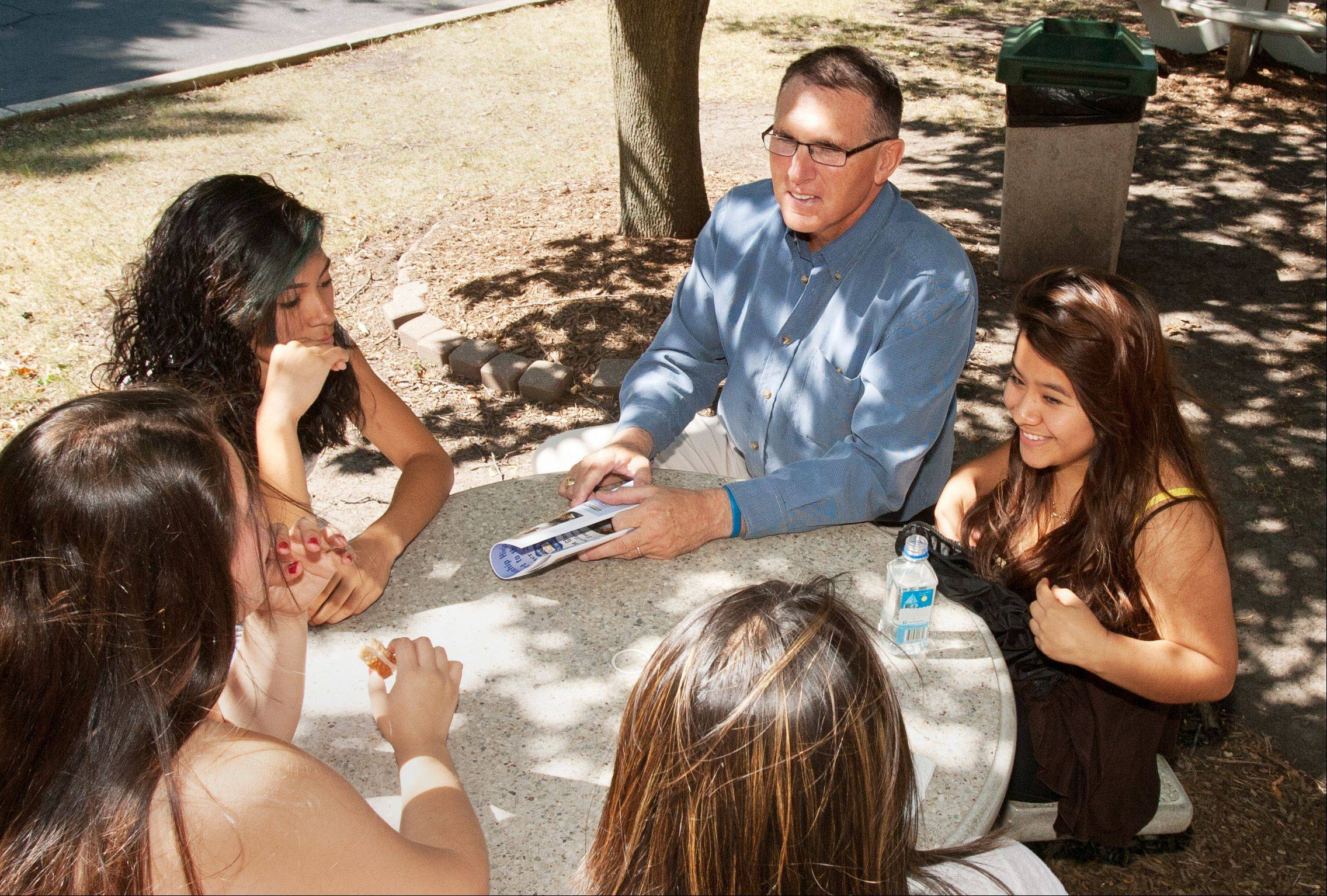 Former Glenbard High School District 87 Superintendent Mike Meissen talks with students taking summer classes at Glenbard West, including Ivet Nunez, left, and Yoana Tapia. He stepped down last week after six years leading the state's third-largest high school district.