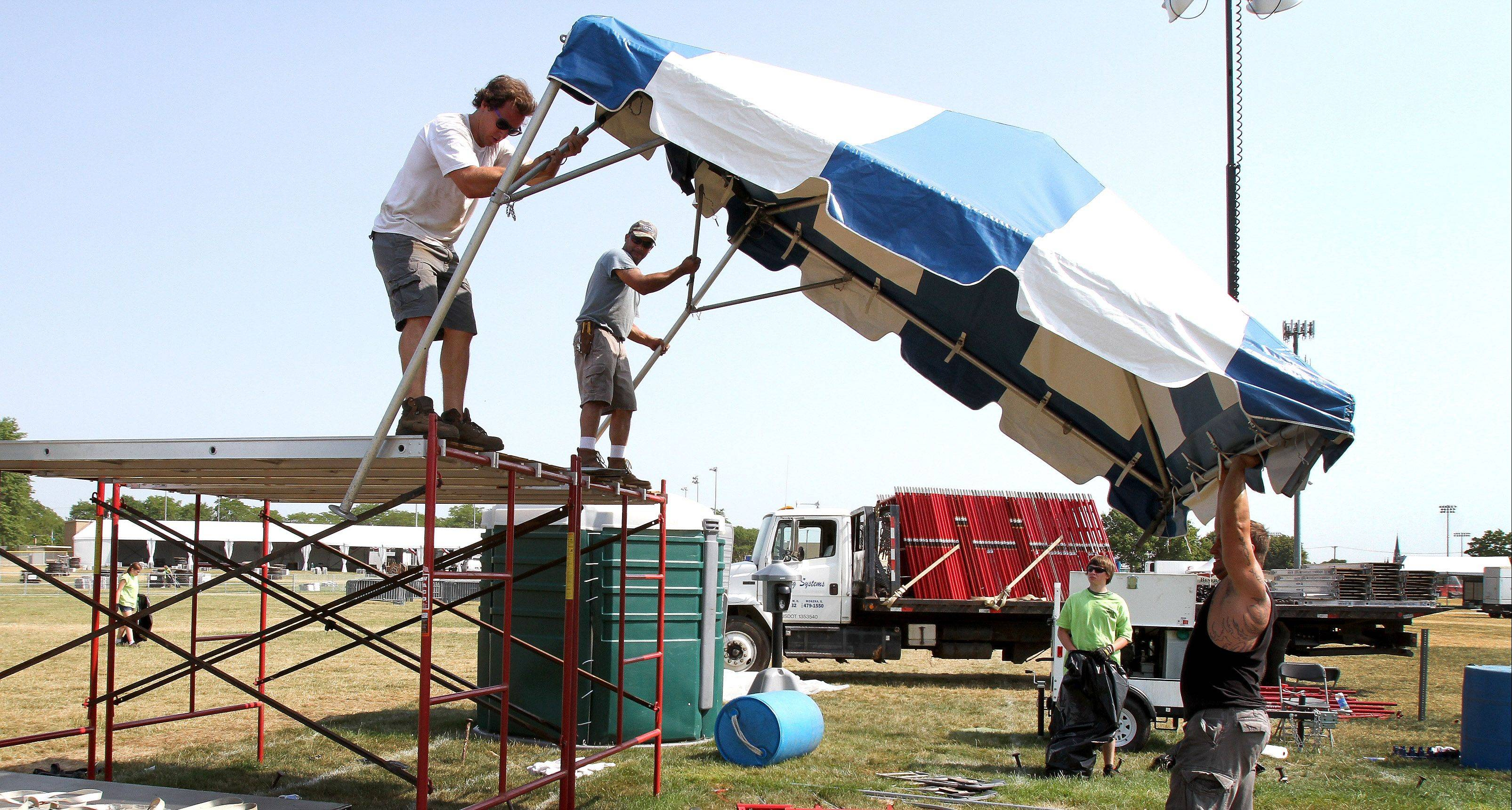 Crews work Thursday to clean up Naperville's Ribfest grounds. Festival organizers say extreme heat and the aftermath of severe storms combined to cut attendance by nearly 25 percent.