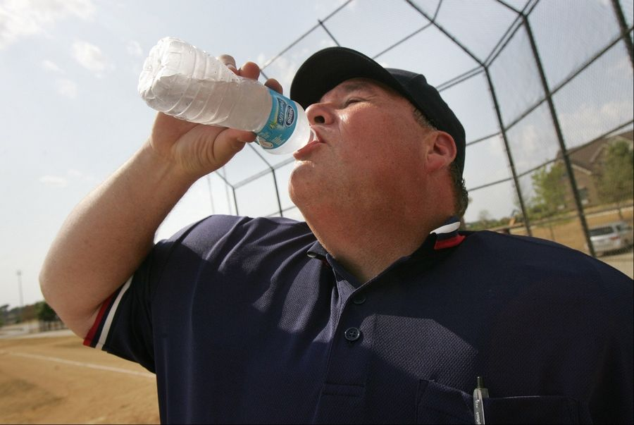 Baseball umpire James Benedict, of Lake Zurich, tries to stay hydrated during the Lake Zurich Cougar Travel Team Wood Bat Tournament Thursday at Heritage Oaks Park in Hawthorn Woods. The 100-degree weather caused players, coaches, and spectators to seek shade and drink lots of water.