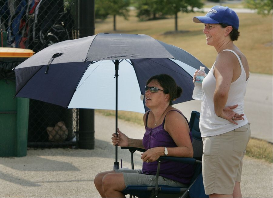 Vernon Hills Cougars parents Margaret Herron, left, and Ronna Streiff try to stay cool in the heat during the Lake Zurich Cougar Travel Team Wood Bat Tournament Thursday at Heritage Oaks Park in Hawthorn Woods. The 100-degree weather caused players, coaches, and spectators to seek shade and drink lots of water.